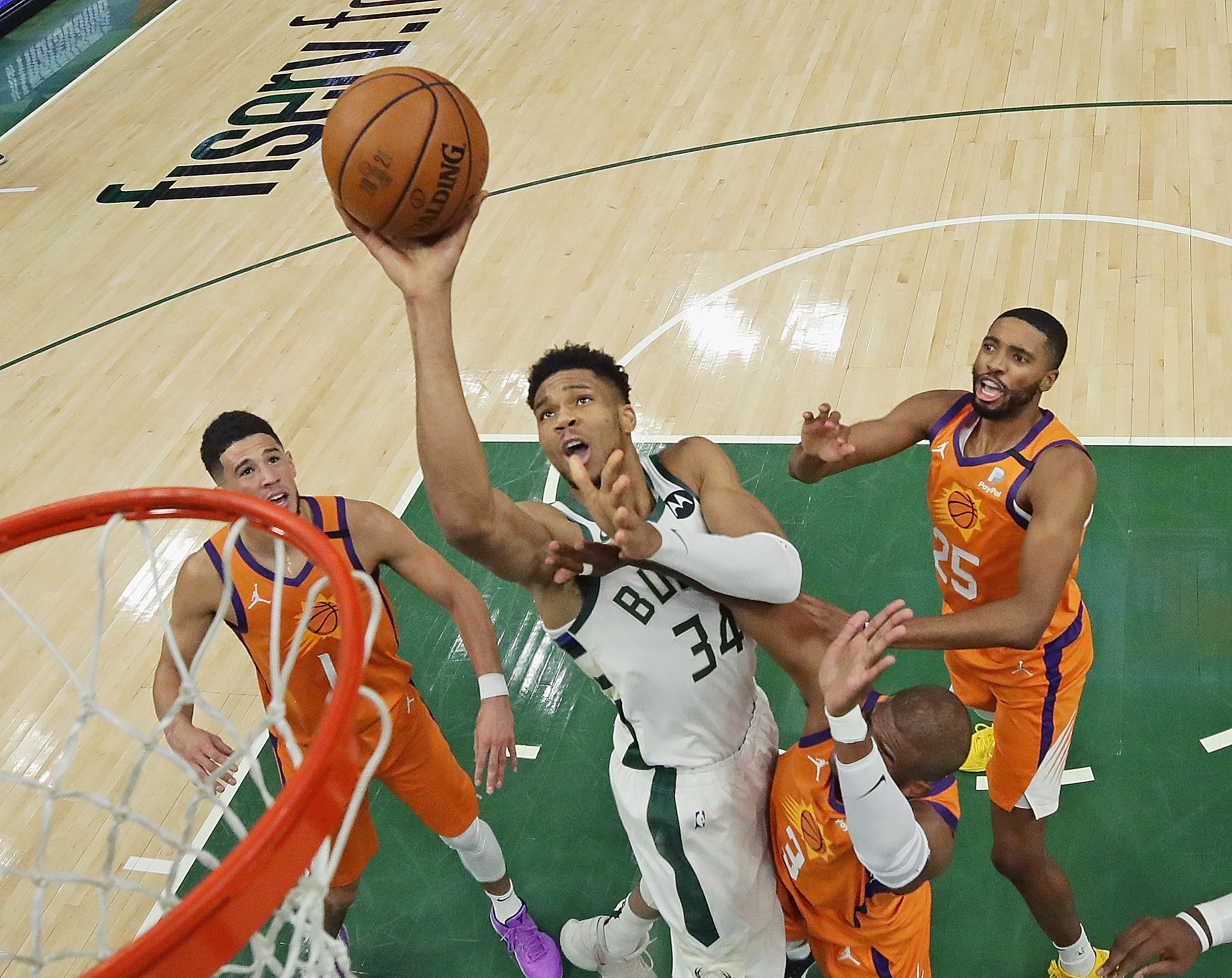 Giannis Antetokounmpo of the Milwaukee Bucks shoots over Devin Booker, Chris Paul and Mikal Bridges of the Phoenix Suns at Fiserv Forum on July 14, 2021 in Milwaukee, Wisconsin. The Bucks defeated the Sun 109-103.
