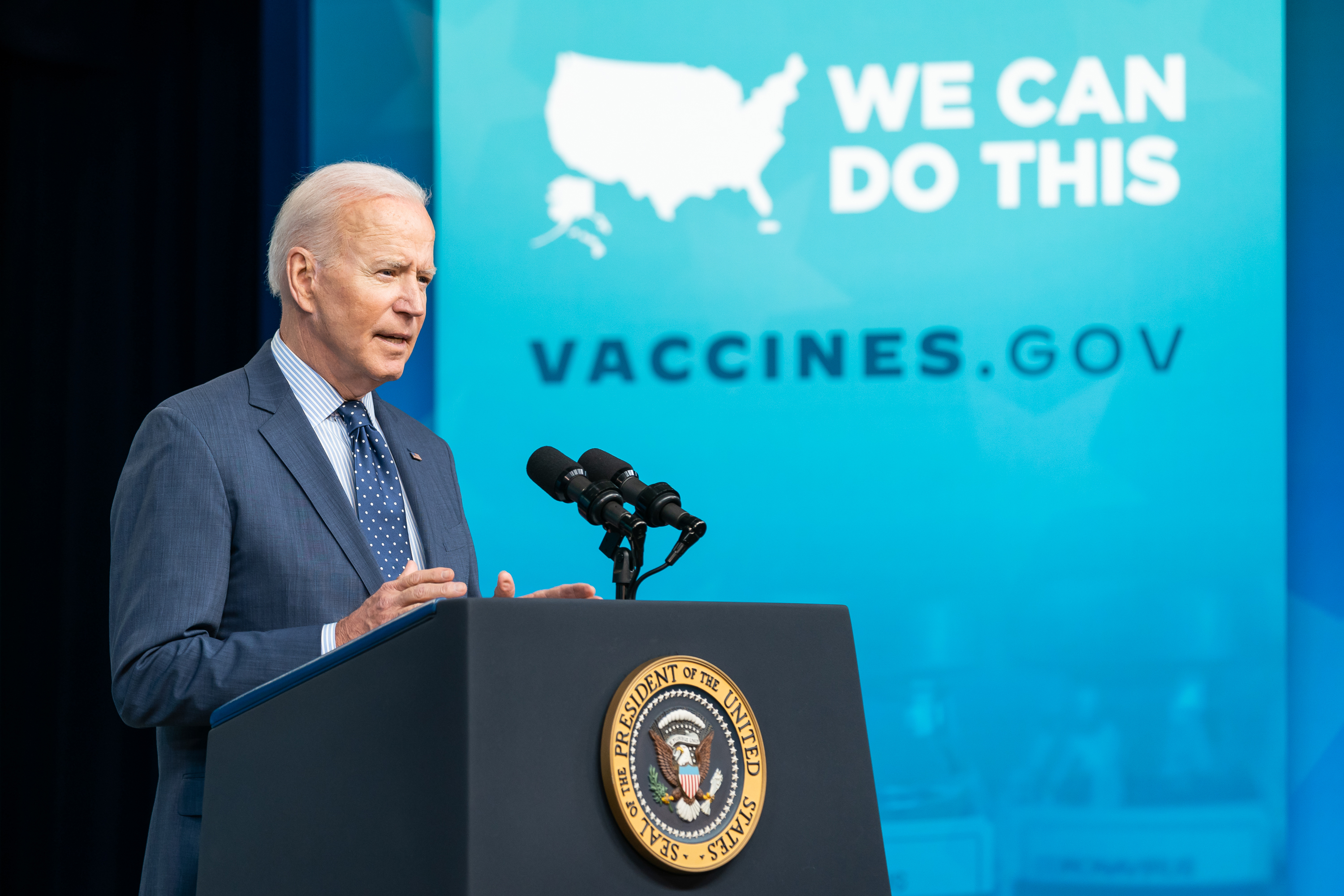 """President Joe Biden speaks in front of a banner promoting Vaccines.gov with the slogan """"WE CAN DO THIS"""""""