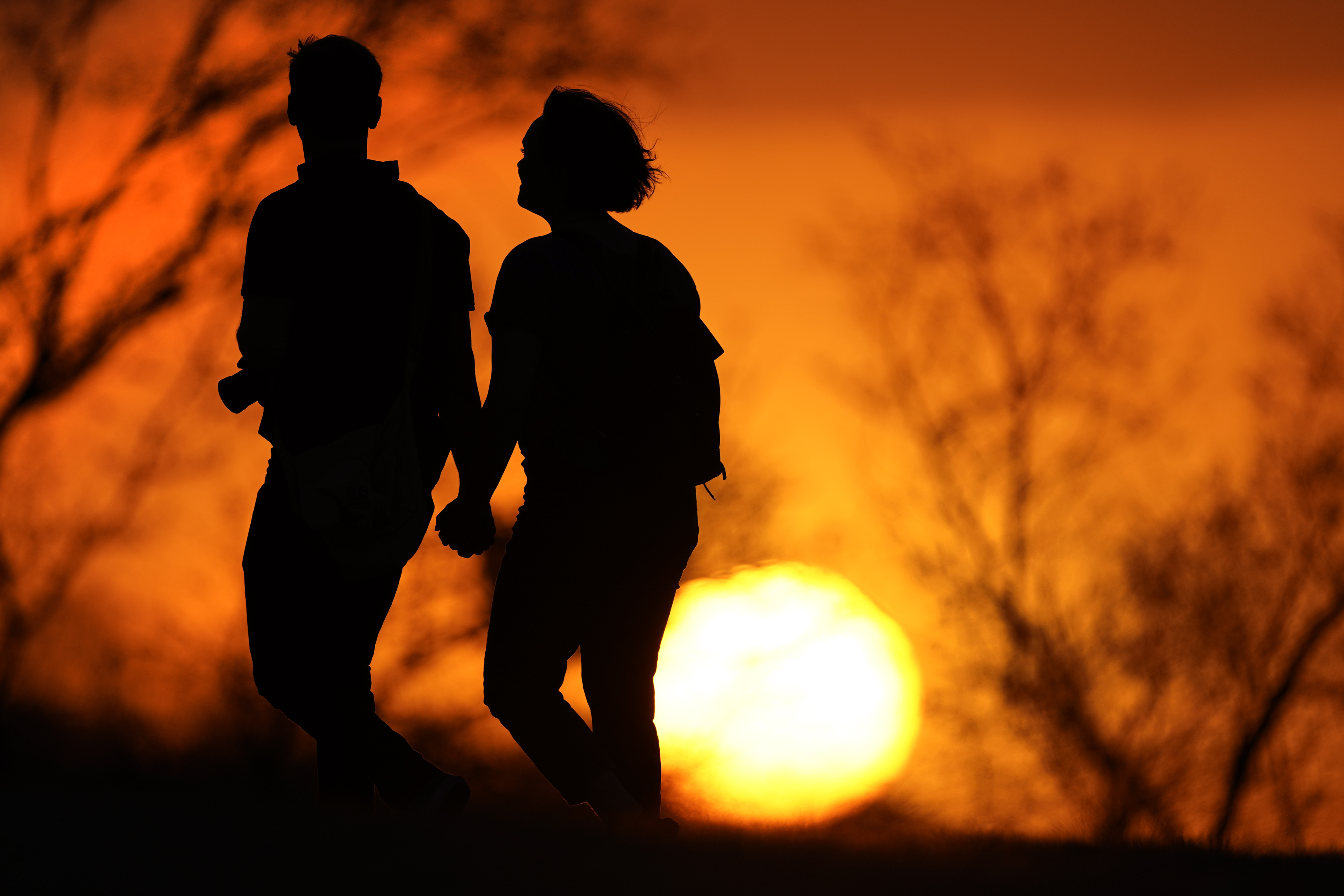 In this Wednesday, March 10, 2021 file photo, a couple walks through a park at sunset in Kansas City, Mo. According to a report released by the Centers for Disease Control and Prevention on Tuesday, July 20, 2021, U.S. life expectancy fell by a year and a half in 2020, the largest one-year decline since World War II. Worse, the decrease for both Black Americans and Hispanic Americans was a staggering three years.