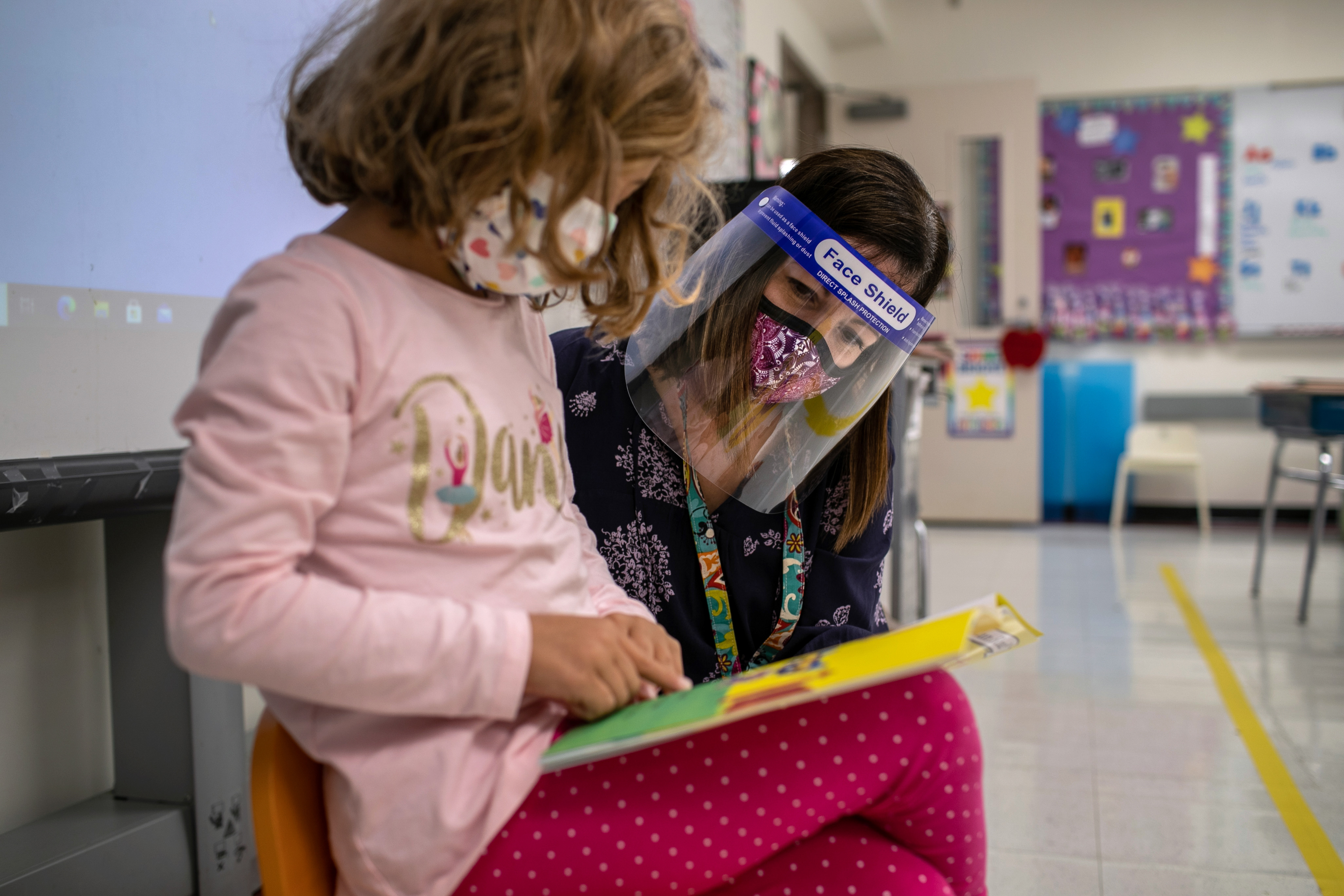 A young girl wearing a pink shirt and protective mask reads a book while her teacher, a woman wearing a face shield and mask, looks over her shoulder in a classroom.