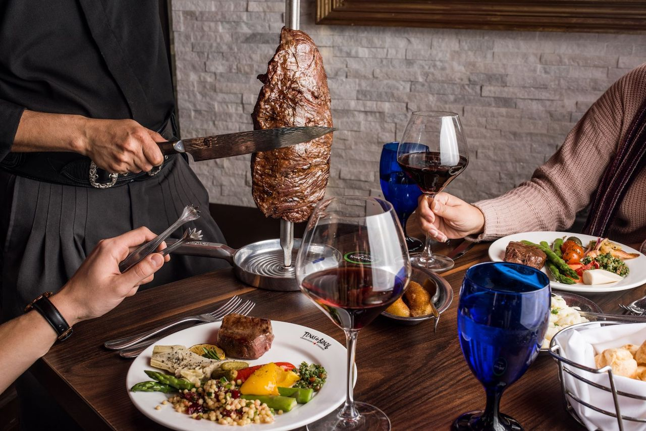 table with meat being carved on it with two diners holding wine glasses and eating