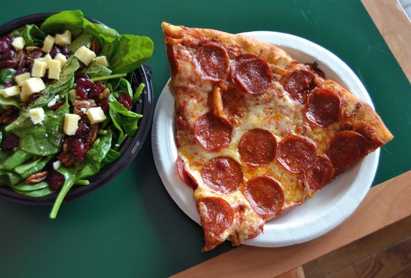 A slice of pepperoni with a side salad