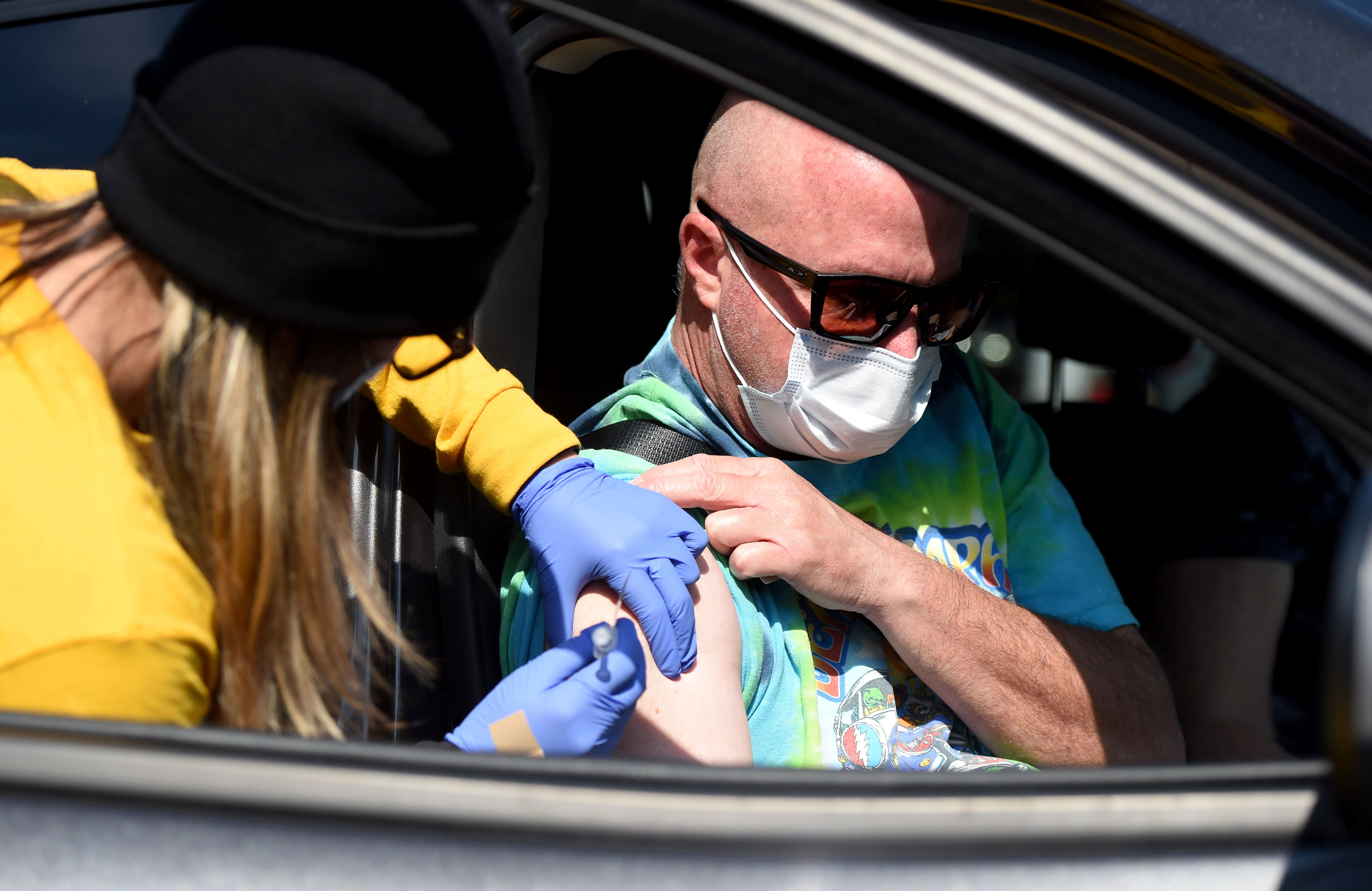 A teacher receives a vaccine from his car on a sunny day. He is wearing a white protective mask.