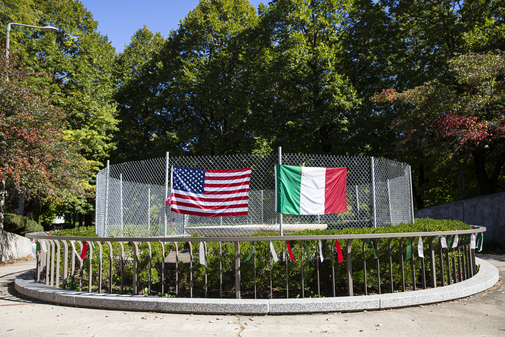 A fence with the U.S. and Italian flags cover the area where a Christopher Columbus statue once stood at Arrigo Park in Little Italy on Oct. 8, 2020.