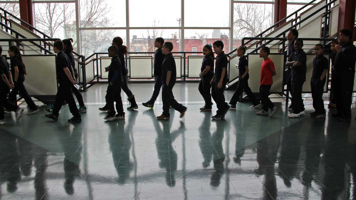 Students walk in a hallway, with their shadows visible on the floor.