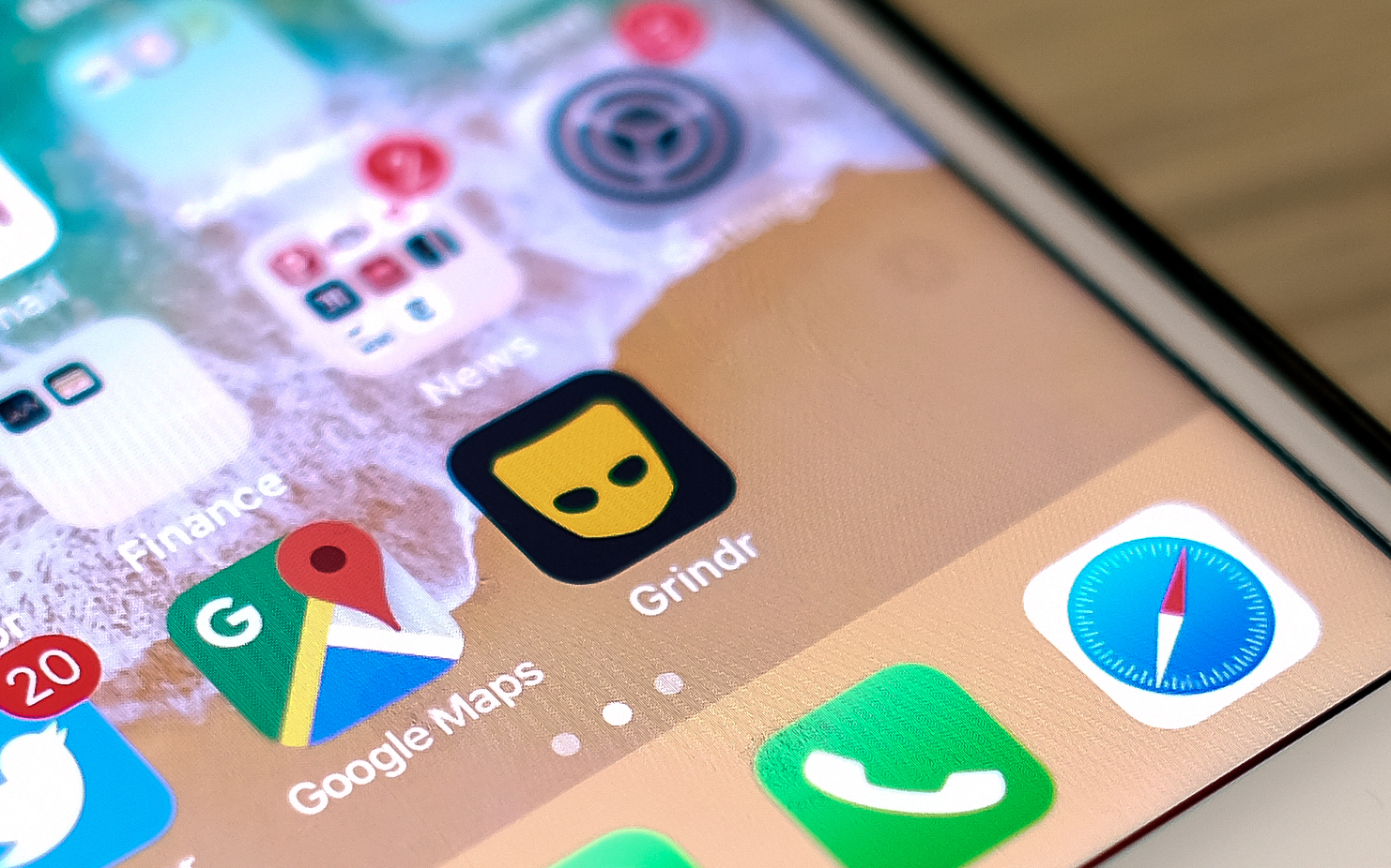 Dating app Grindr next to the Google Maps app on an iPhone screen.