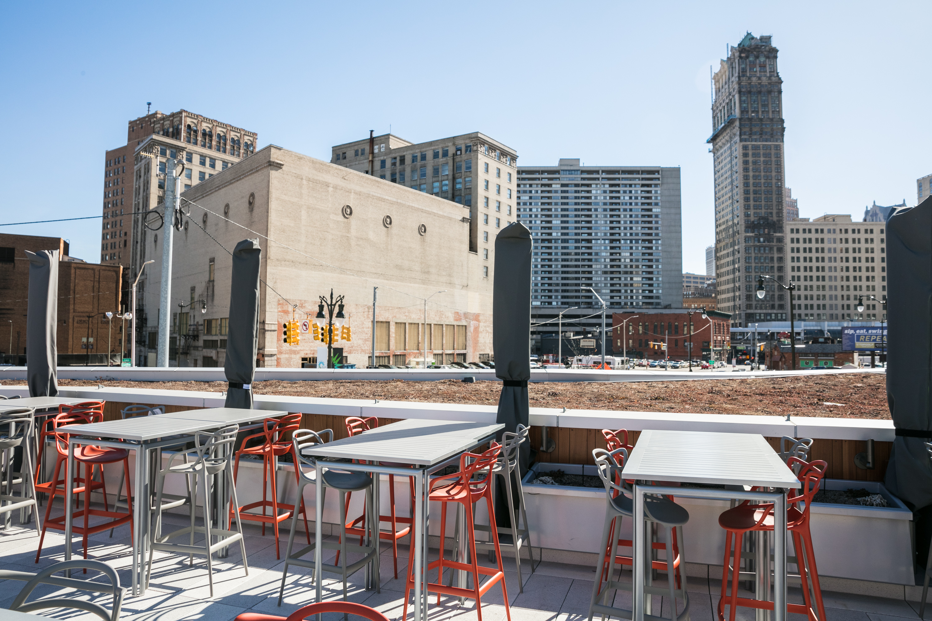 Rooftop building with tables and chairs shows views of downtown Detroit buildings