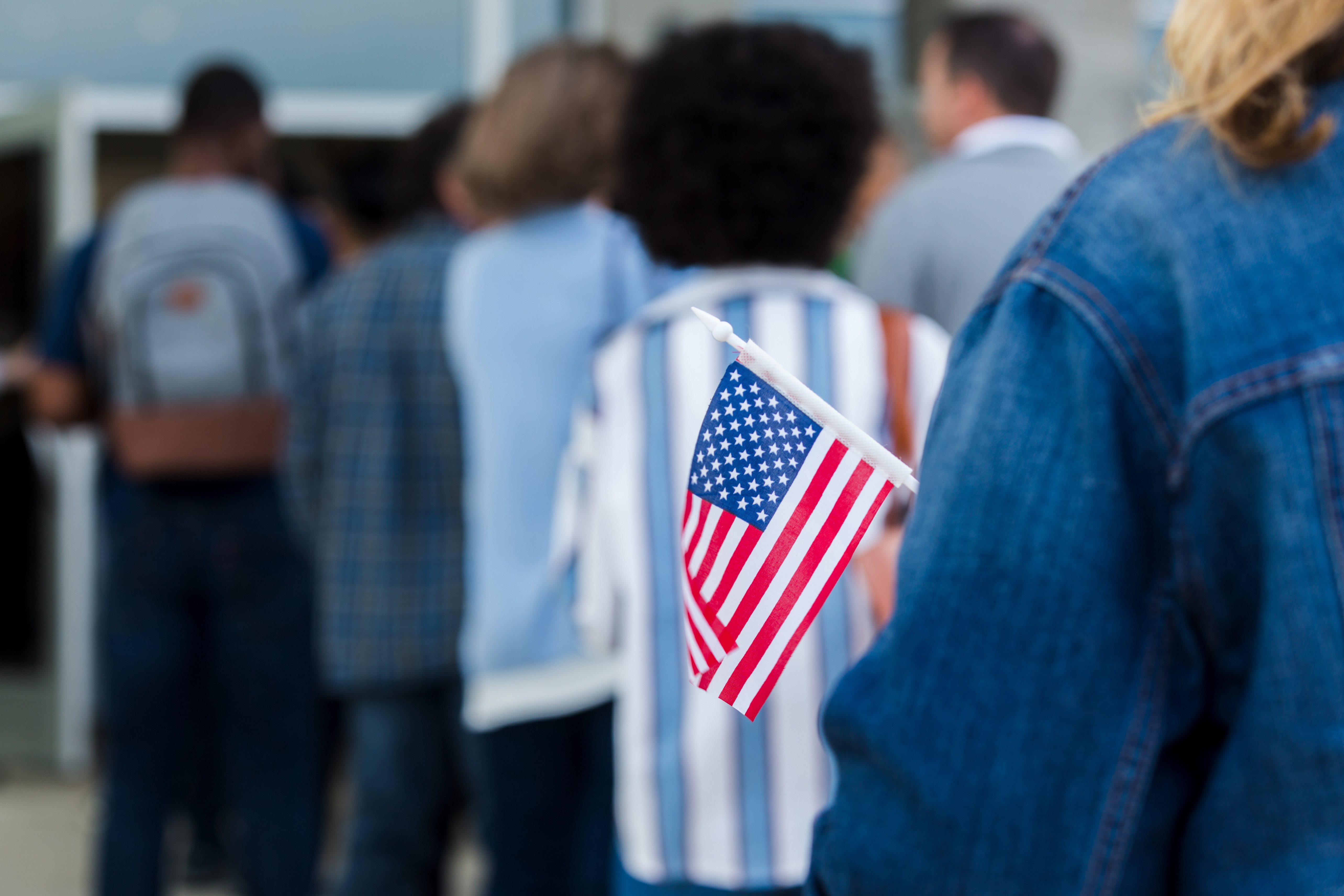 A person in line at a polling place holds a small American flag.
