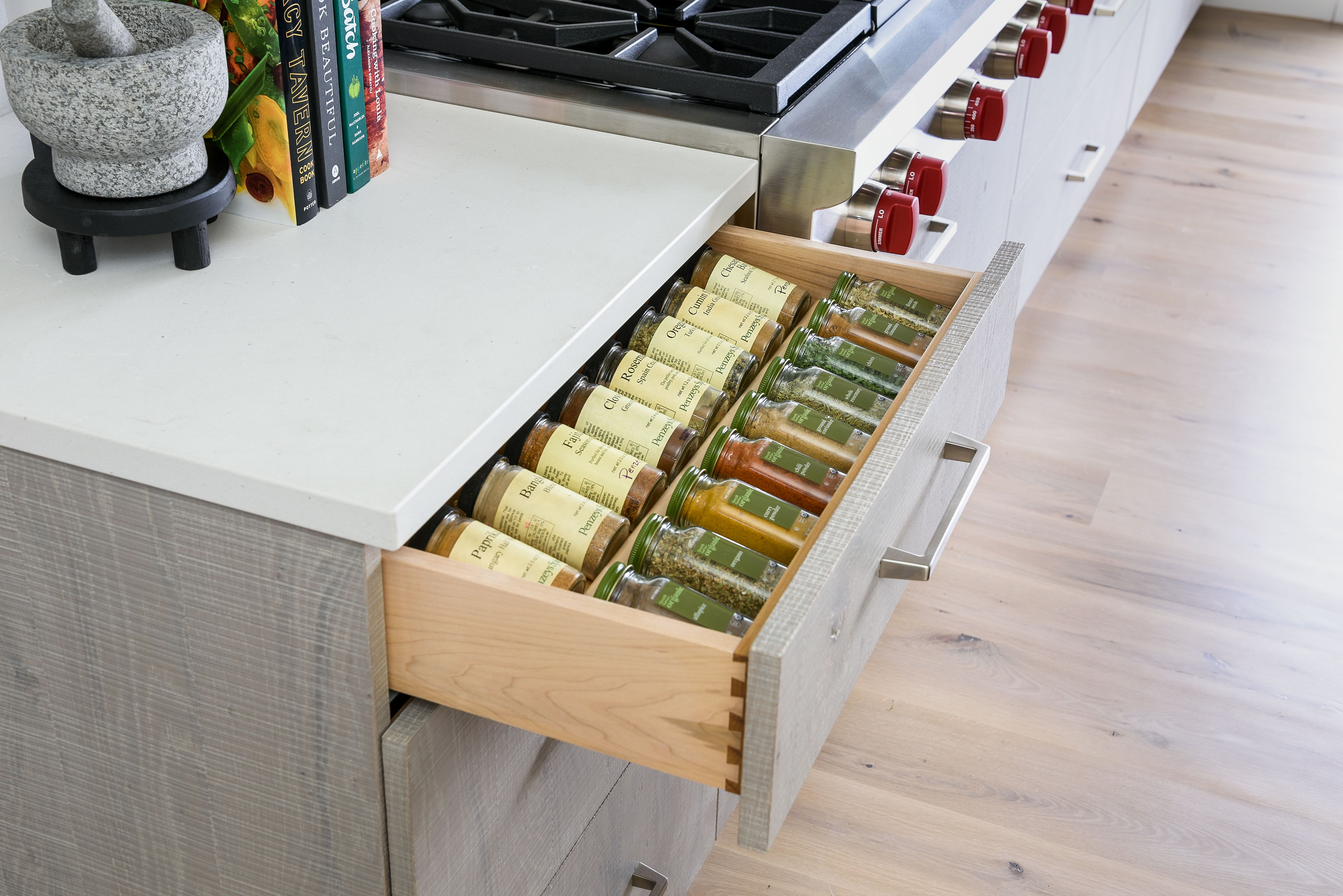 A newly renovated kitchen with a drawer open, filled with spices. A mortar and pestle and cookbooks sit on the counter.