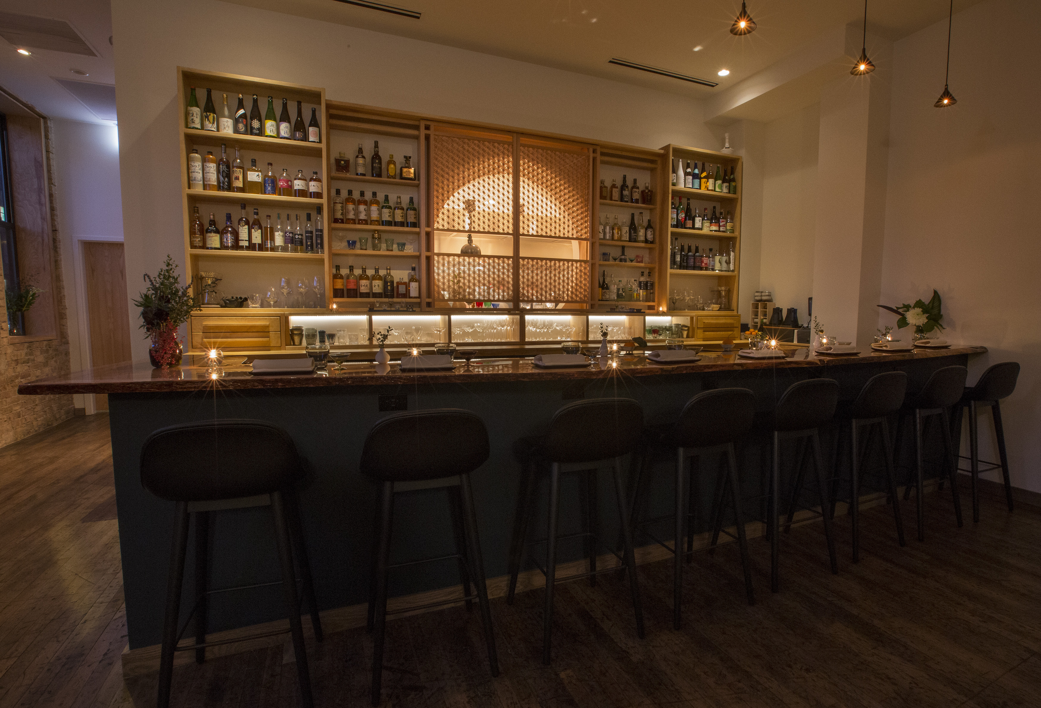 A bar with stools and a wooden shelf in back.