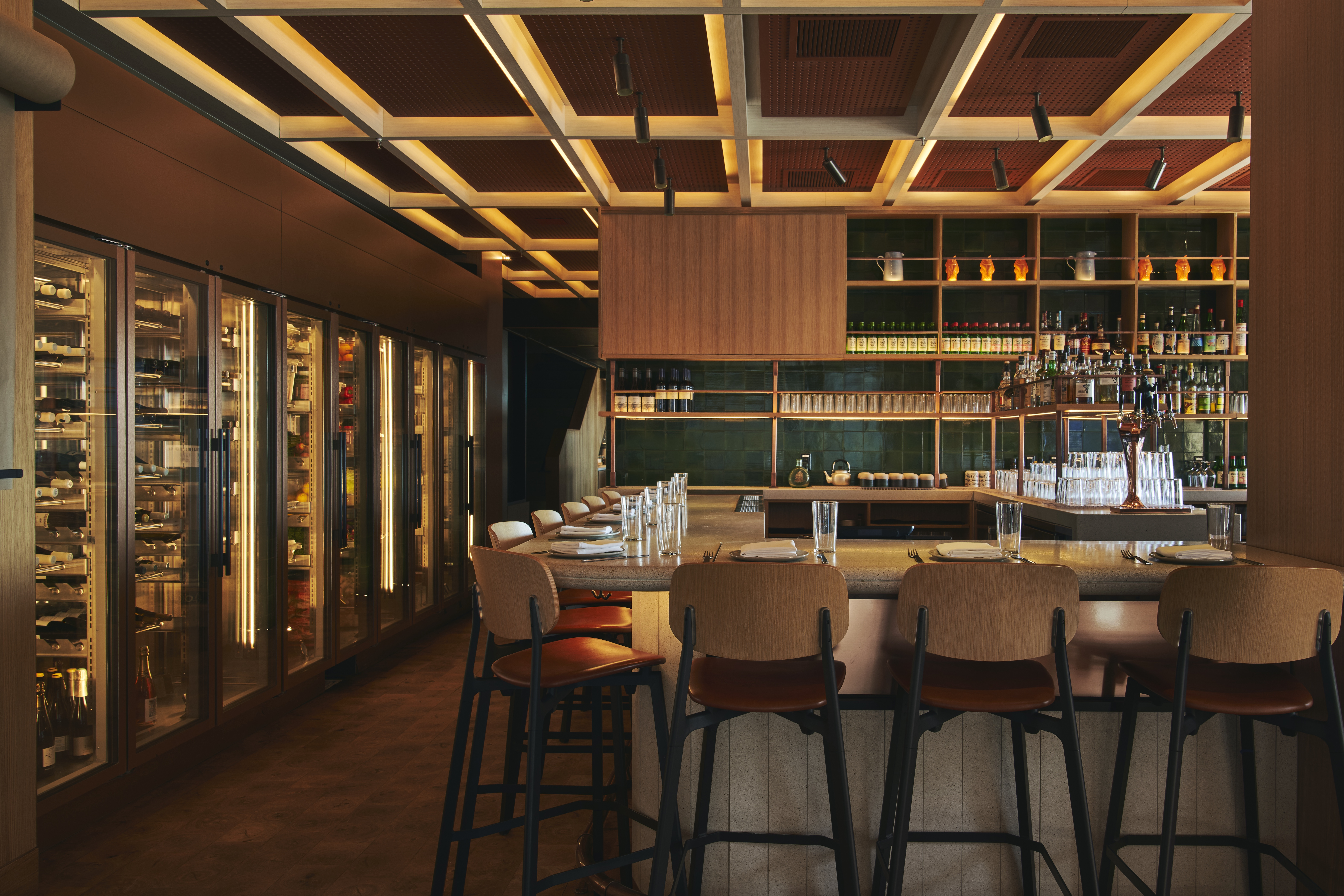 Tan stools with backs line the indoor bar at Momofuku Ssam Bar; warm lights shine from ceiling panels above