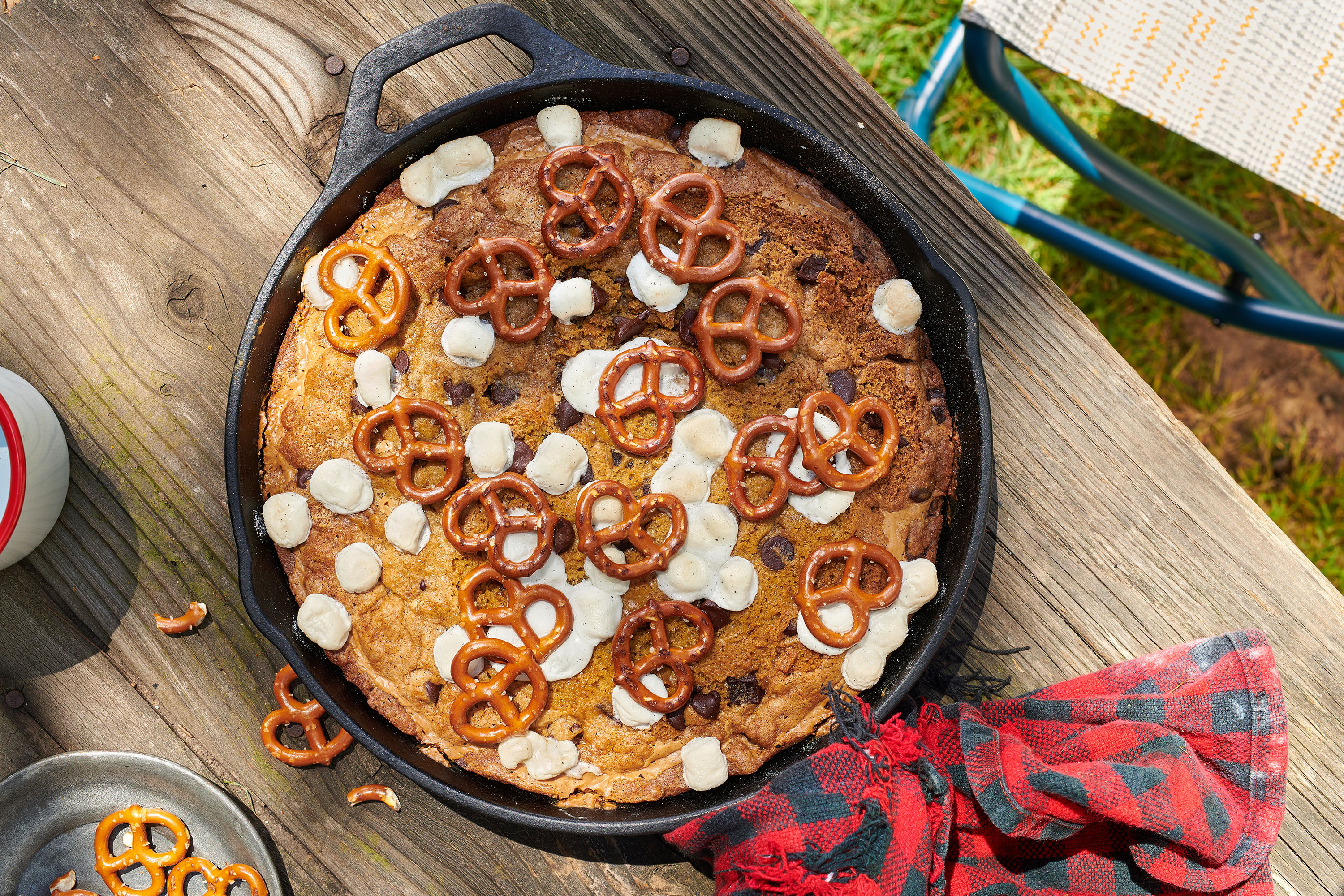 Cast-iron skillet containing a baked chocolate chip cookie with pretzels and marshmallows on top, seen from above on top of a picnic table.