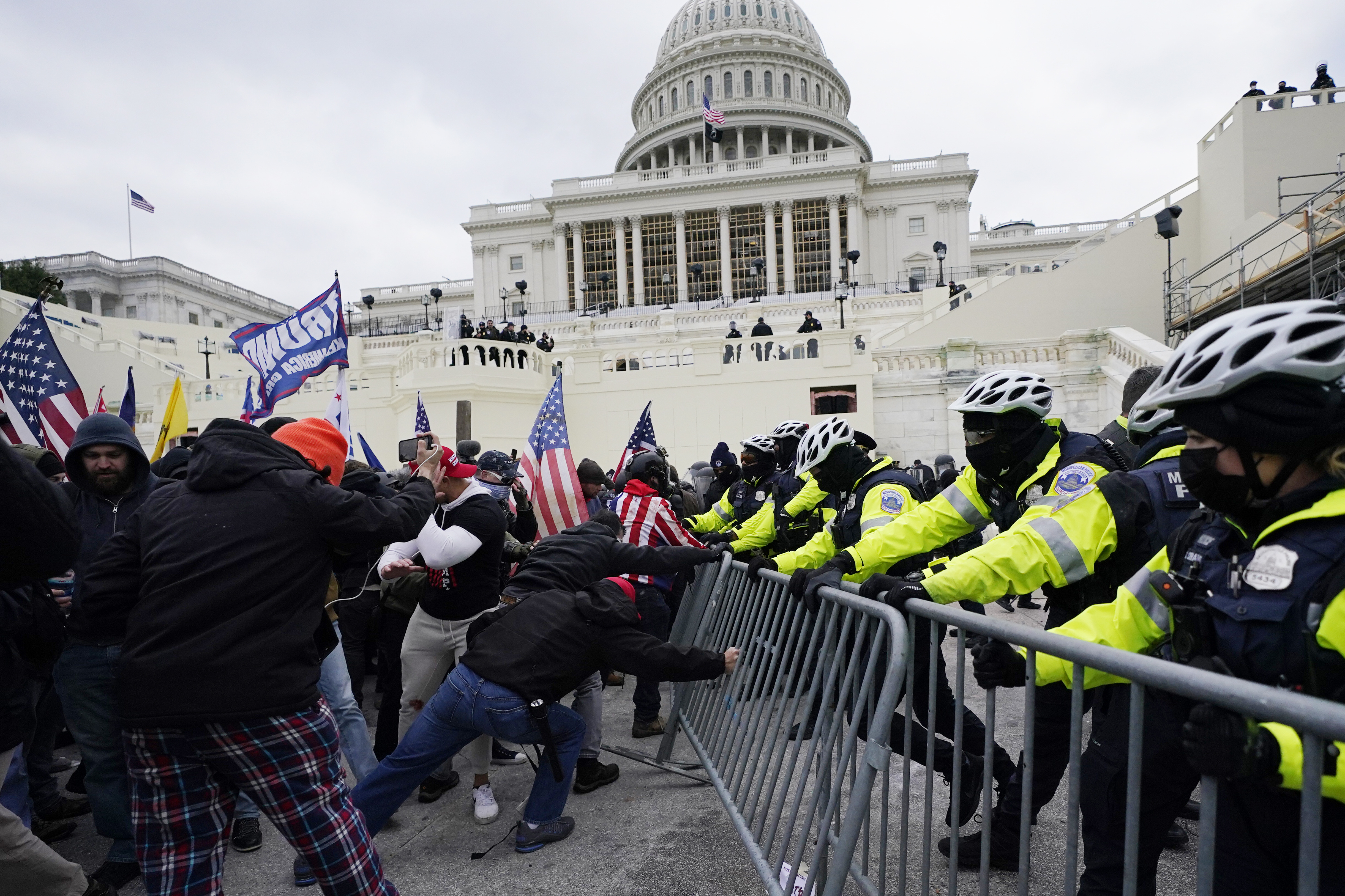 Supporters loyal to then-President Donald Trump, try to break through a police barrier at the Capitol in Washington on Jan 6, 2021.