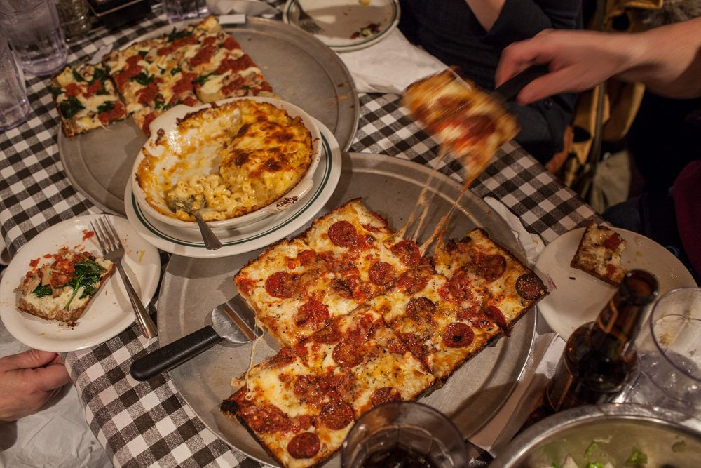 Square Detroit-style pizza on a checkered tablecloth in a restaurant dining room