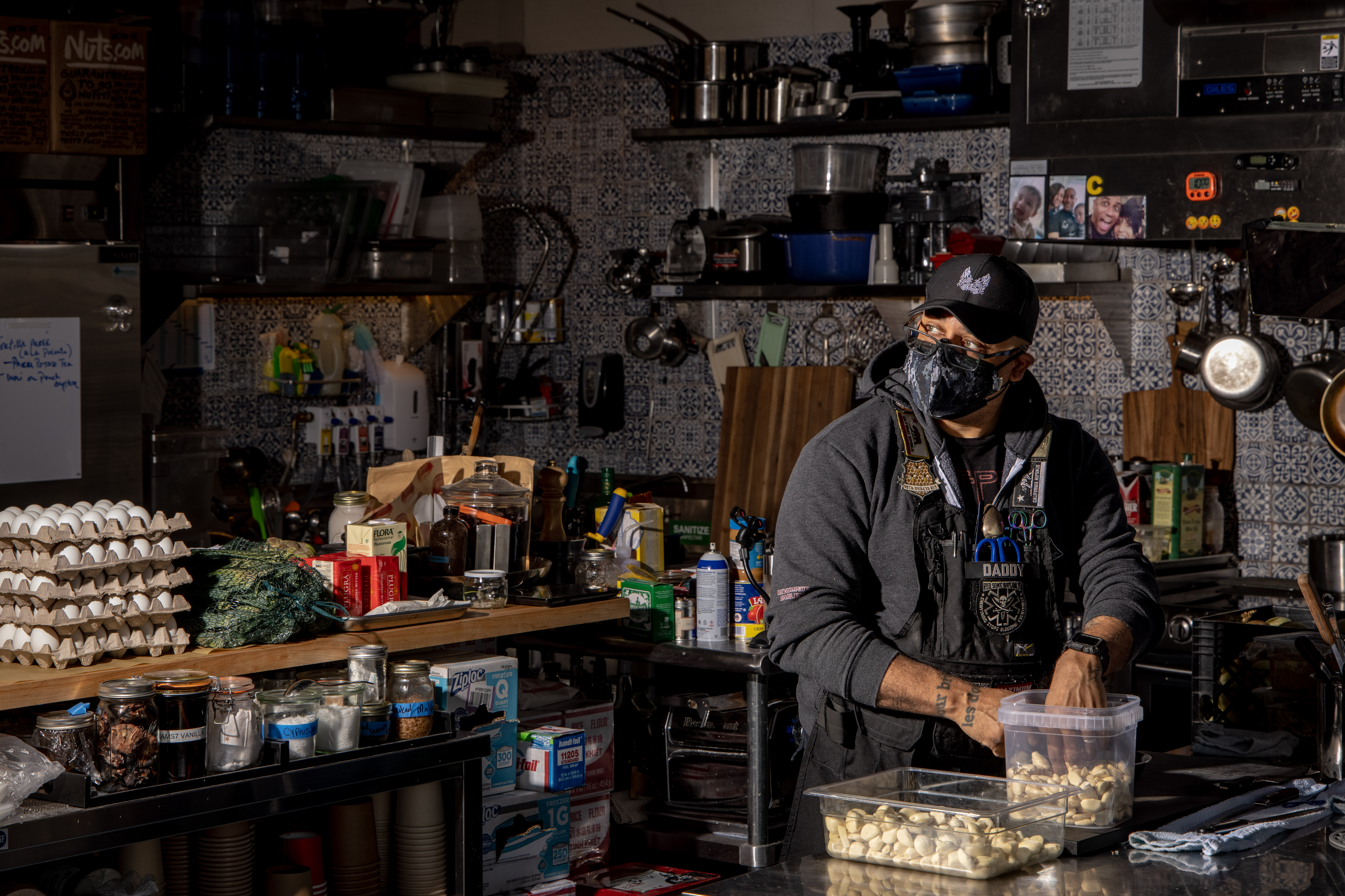 A man dressed in all black with various patches on his uniform picks through a tub of garlic cloves against a crowded kitchen backdrop