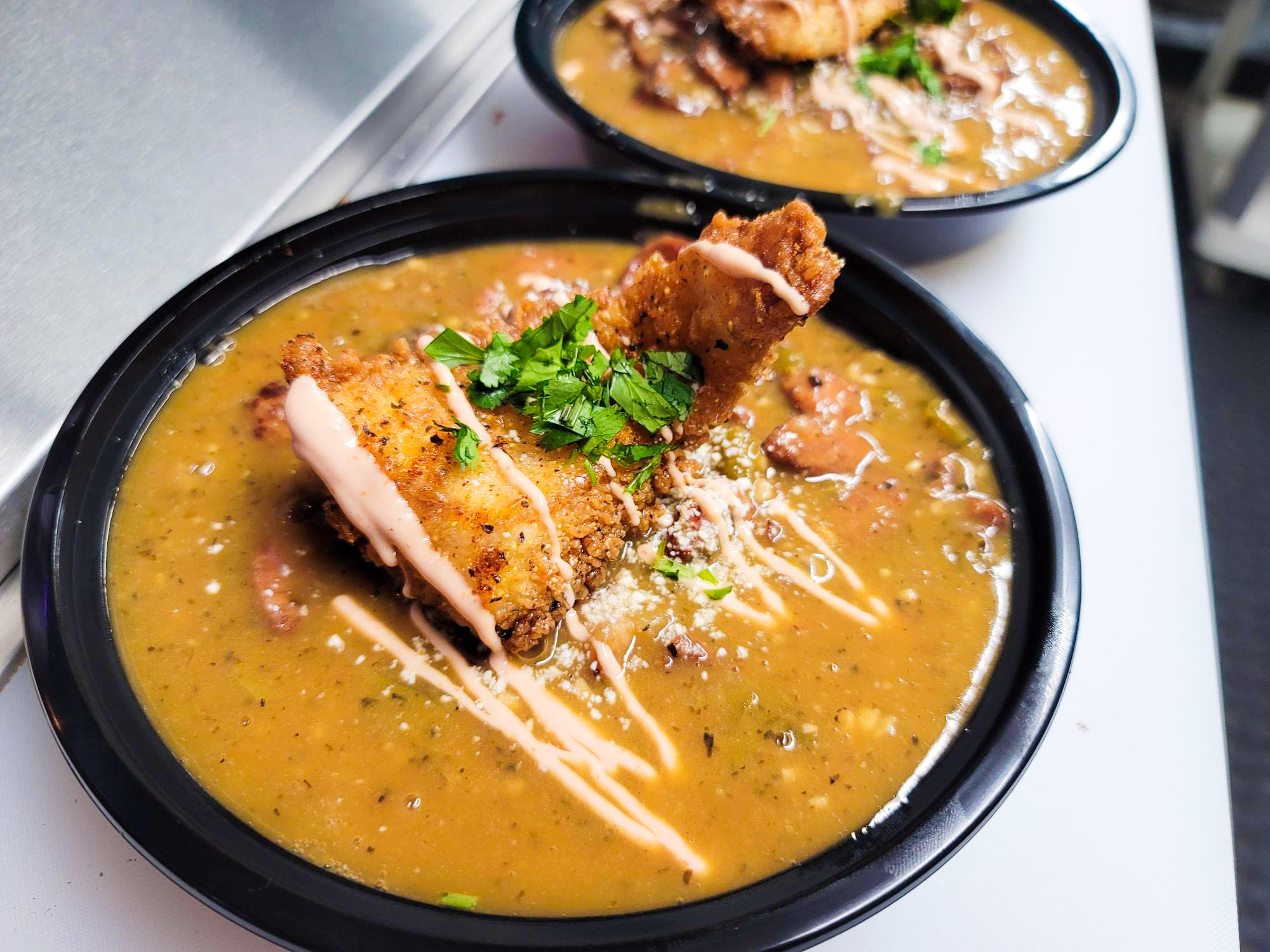 A black bowl on a cold table in a kitchen is filled with etouffee, with a piece of fried catfish on top