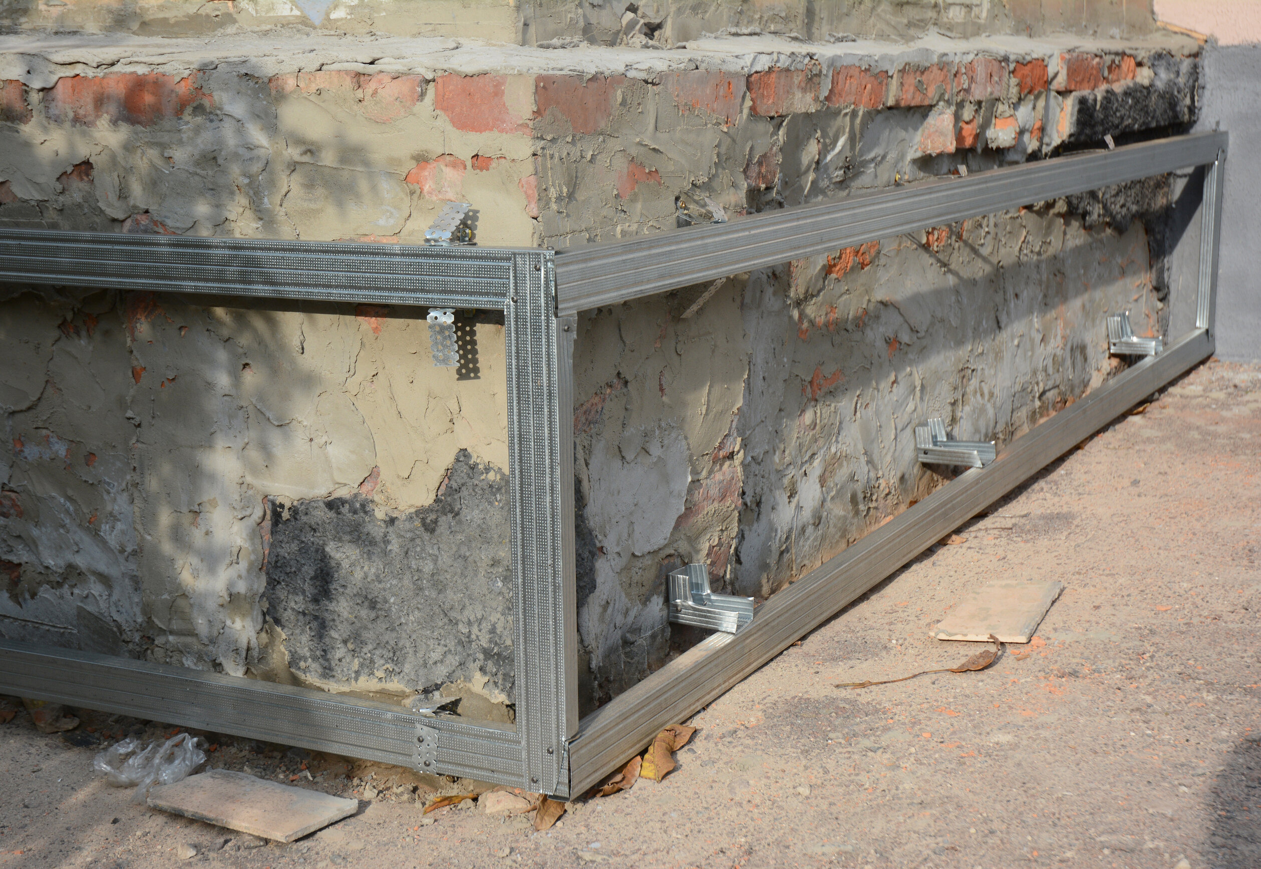 Foundation repair on a brick home using steel rods.