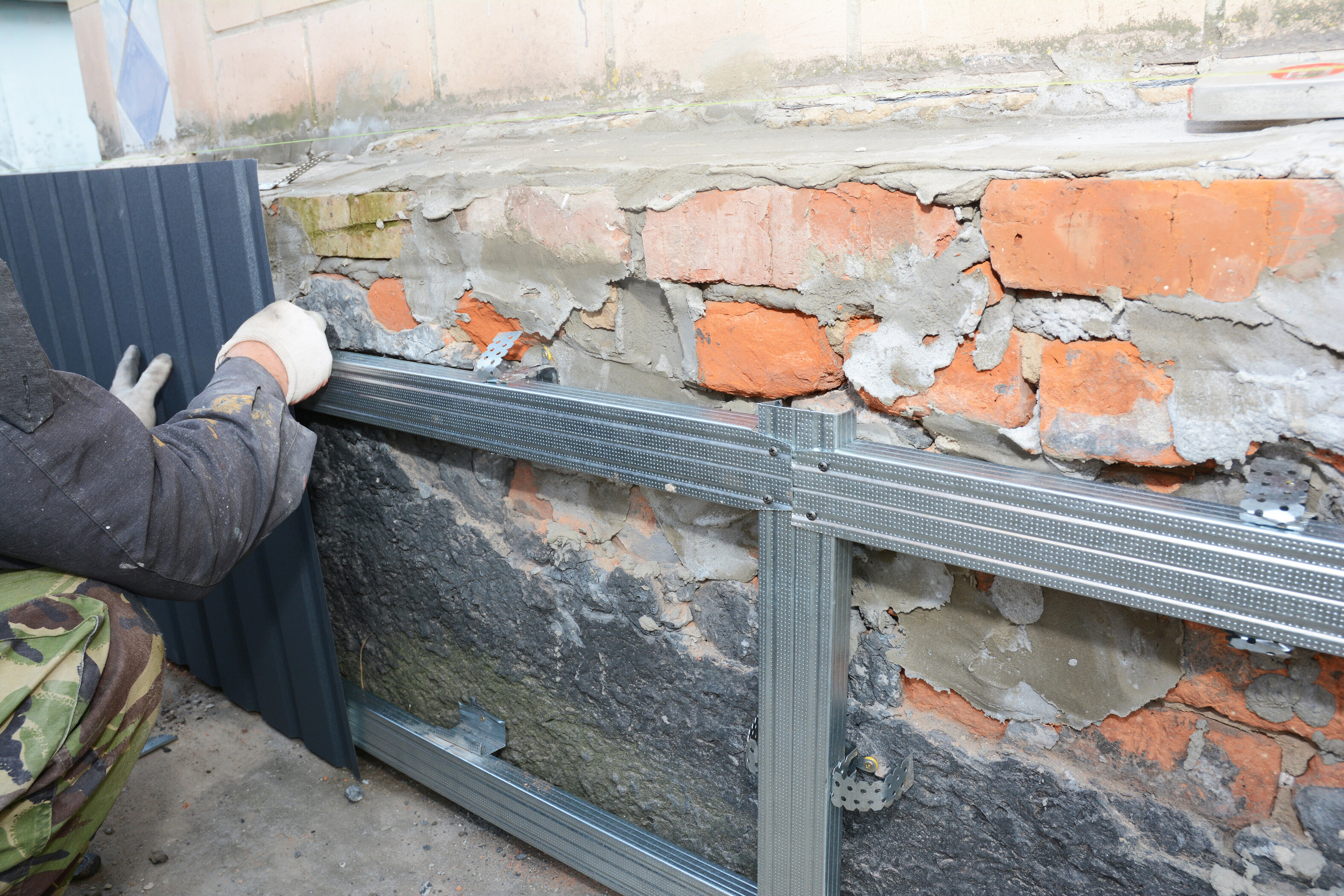 A foundation repair specialist repairing the brick foundation of a home with steel rods.