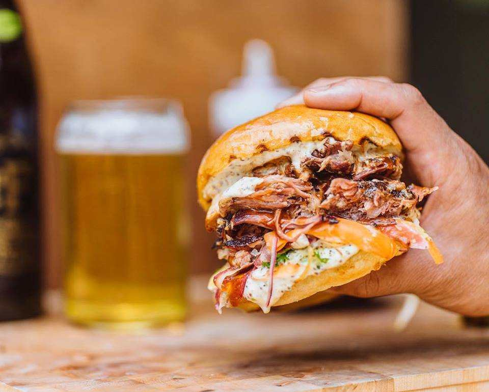A hand holds a pulled pork sandwich