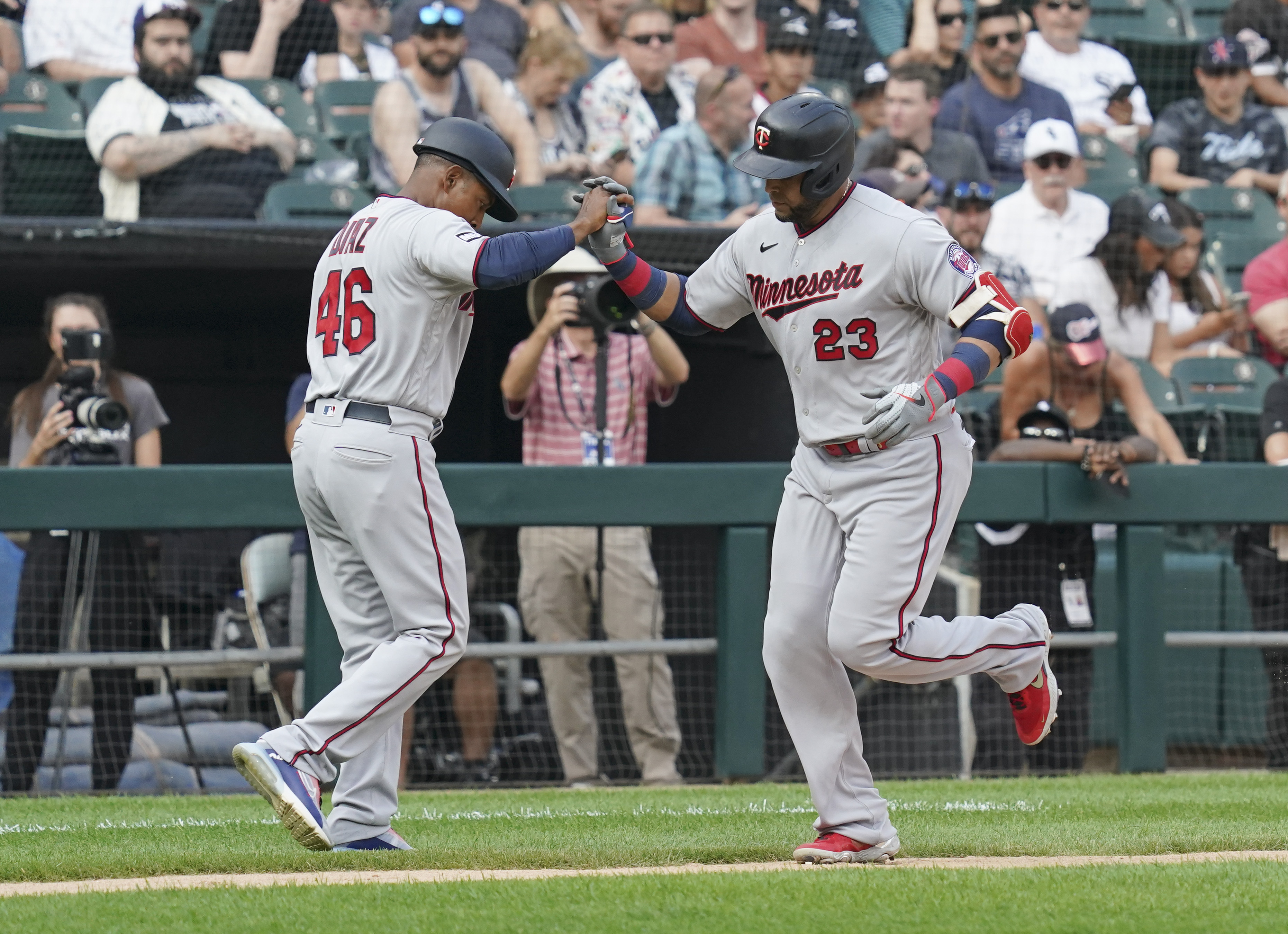 Nelson Cruz #23 of the Minnesota Twins is congratulated by third base coach Tony Diaz #46 of the Minnesota Twins following his home run against the Chicago White Sox at Guaranteed Rate Field on July 19, 2021 in Chicago, Illinois.