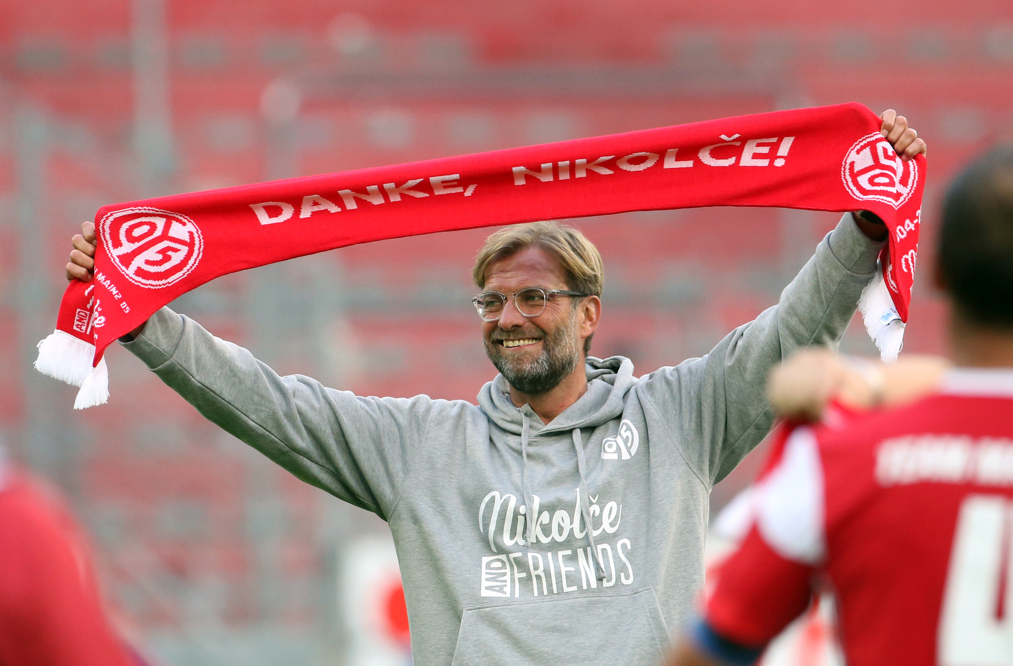 "Liverpool coach Jurgen Klopp holds a football scarf that reads ""Dank, Nikolce"" (lit. thanks, Nikolce) at the FSV Mainz 05 vs ""Nikolce and friends"" football match at the Opel Arena in Mainz, Germany, 2 September 2017"