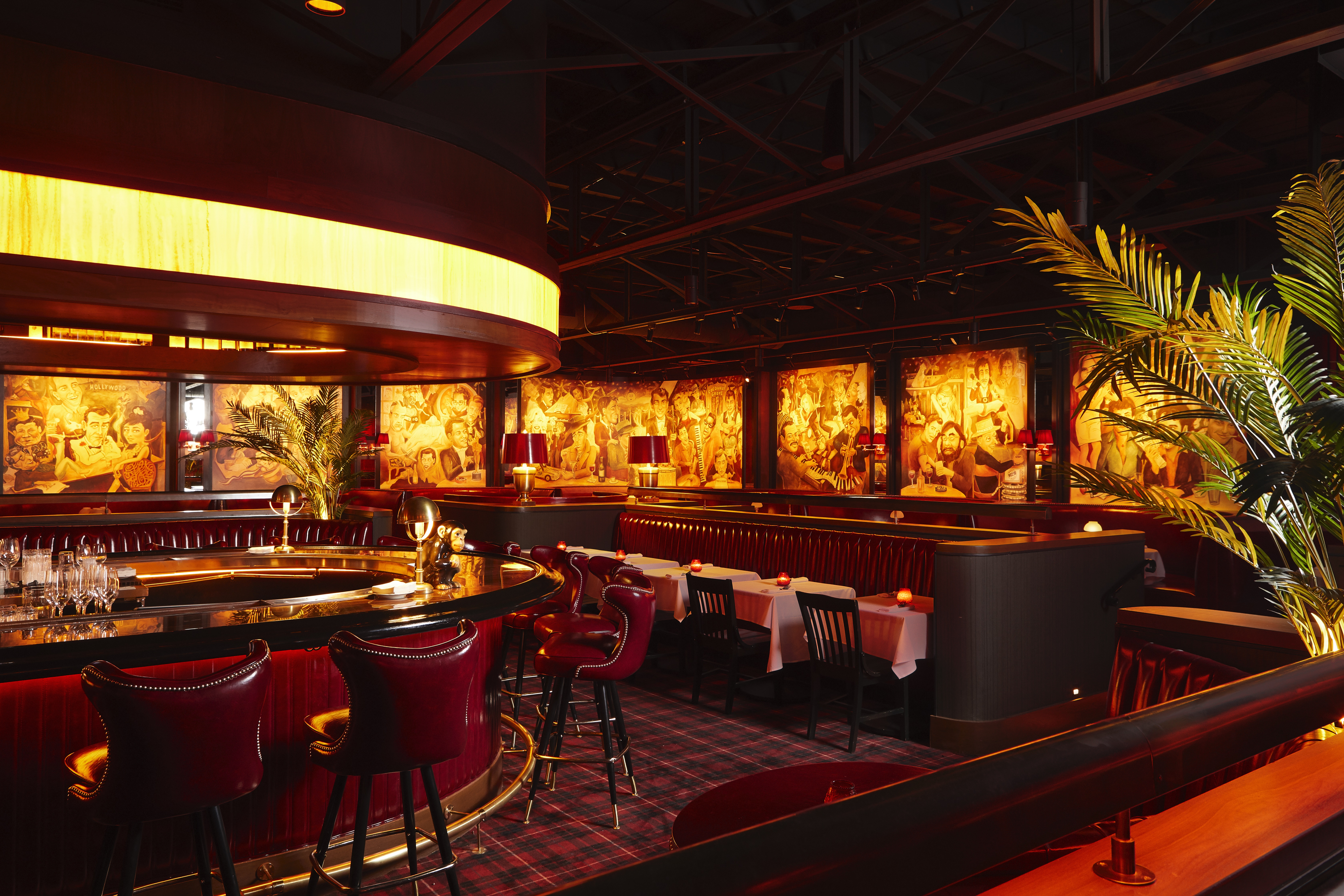 The dining room at Drake's features a round bar with dim lighting and red chairs.