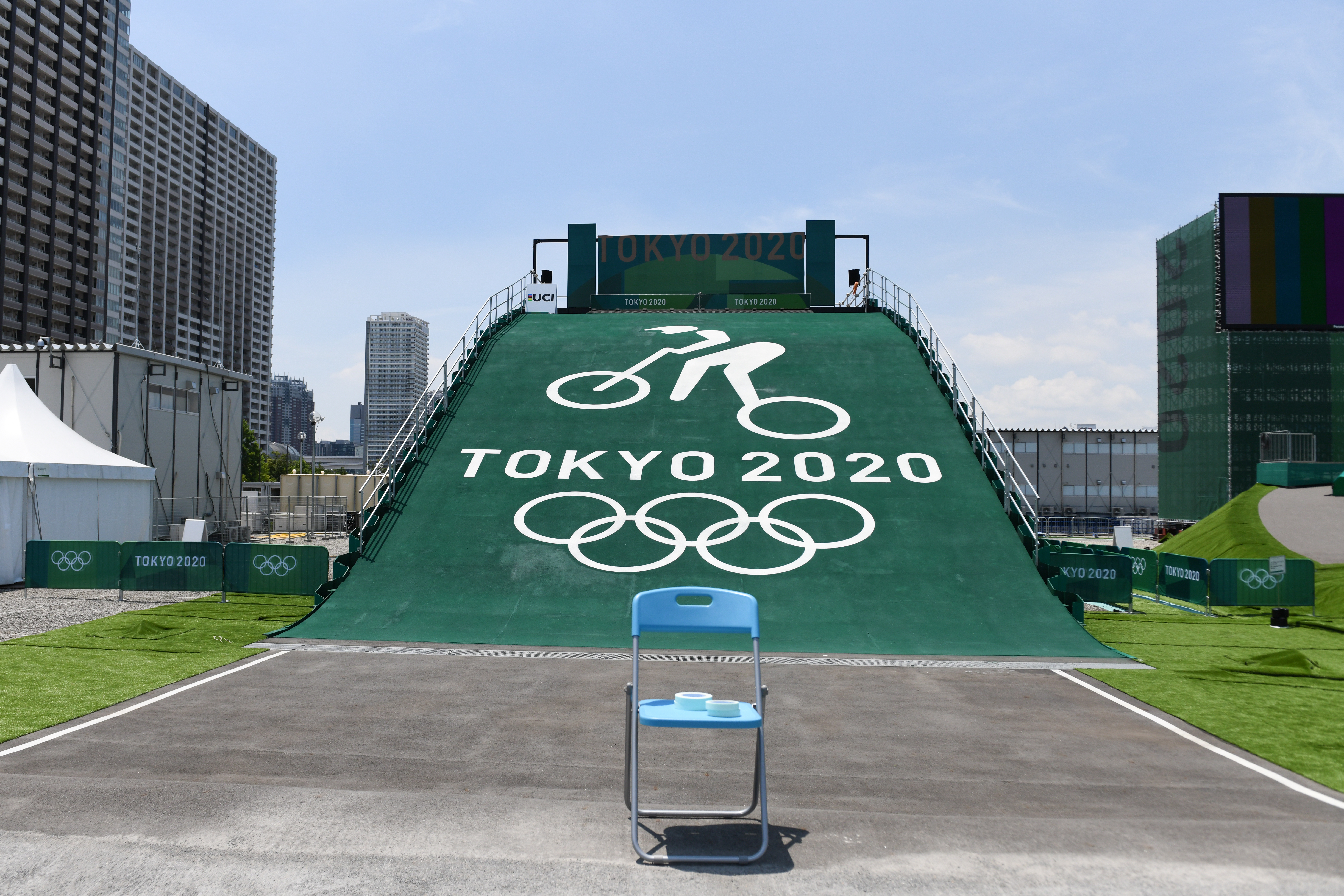 An empty folding chair in front of a ramp with the Tokyo 2020 Olympic rings on the slope.