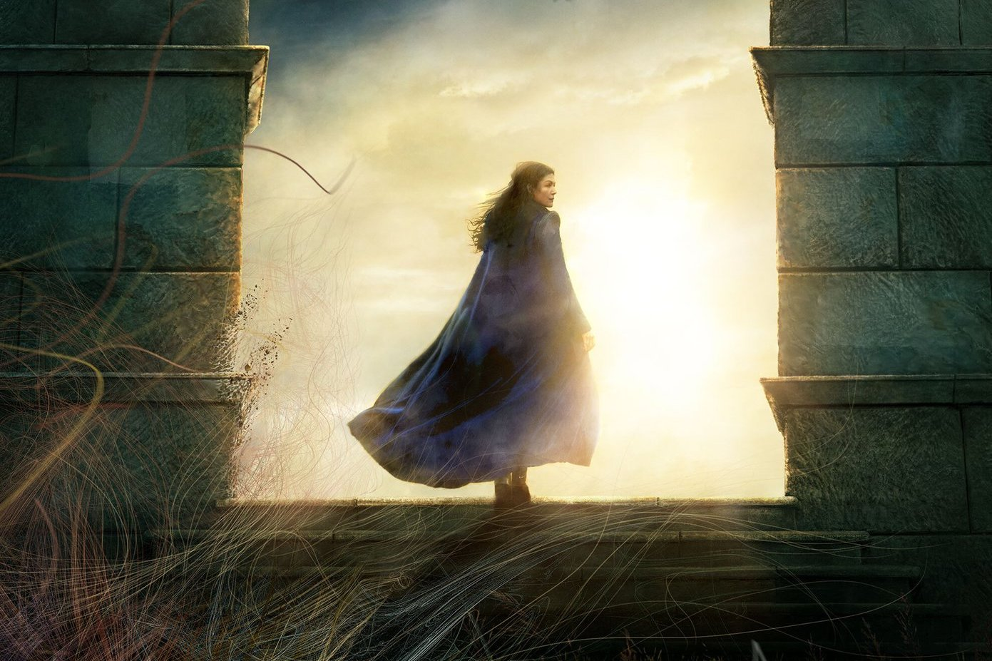 Rosamunde Pike as Moiraine steps through two stone pillars in a poster for Amazon's original series The Wheel of Time.