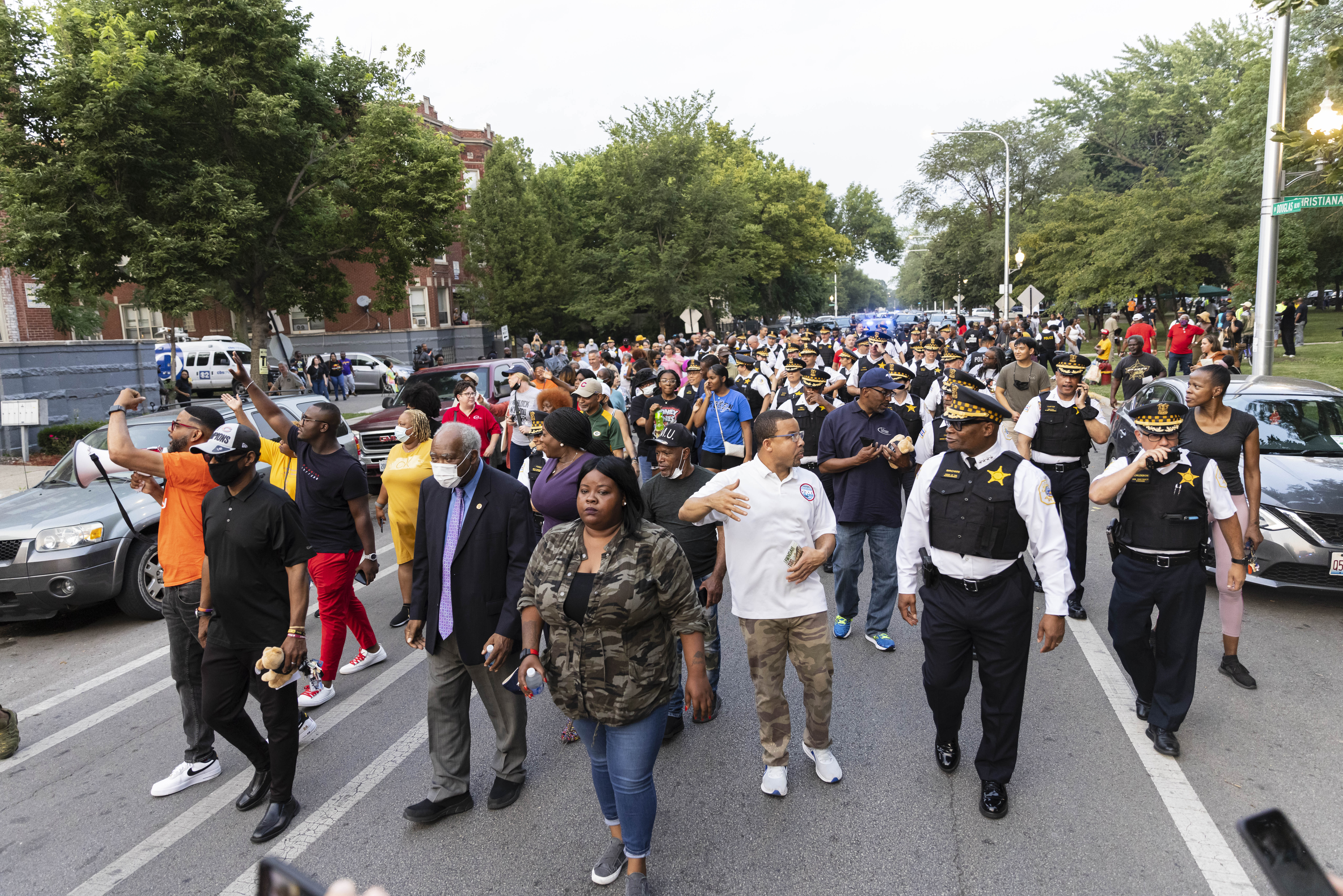 Resident, activists, and Chicago police brass march down Douglas Boulevard on Friday, July 23, 2021 in North Lawndale, site of two mass shootings earlier in the week.