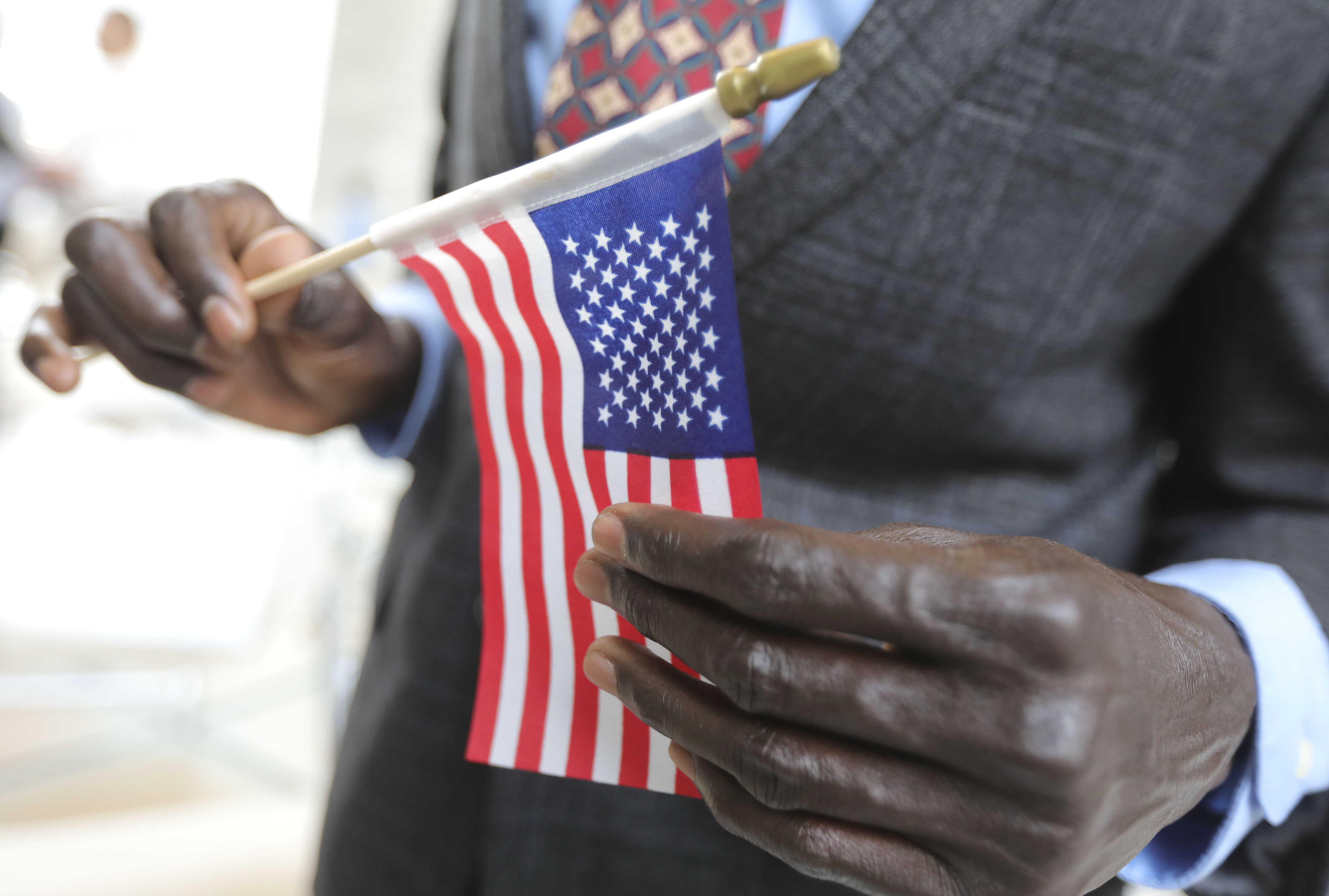 A refugee man holds an American Flag at the Capitol in Salt Lake City.