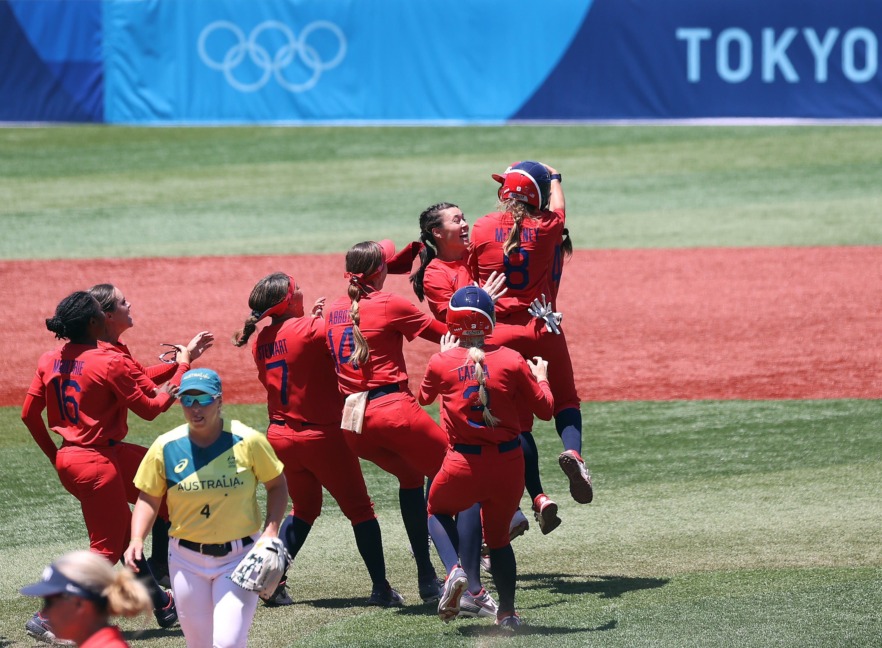 A jubilant mass of humanity descends on Amanda Chidester after her walk off single enabled the US to defeat Australia.