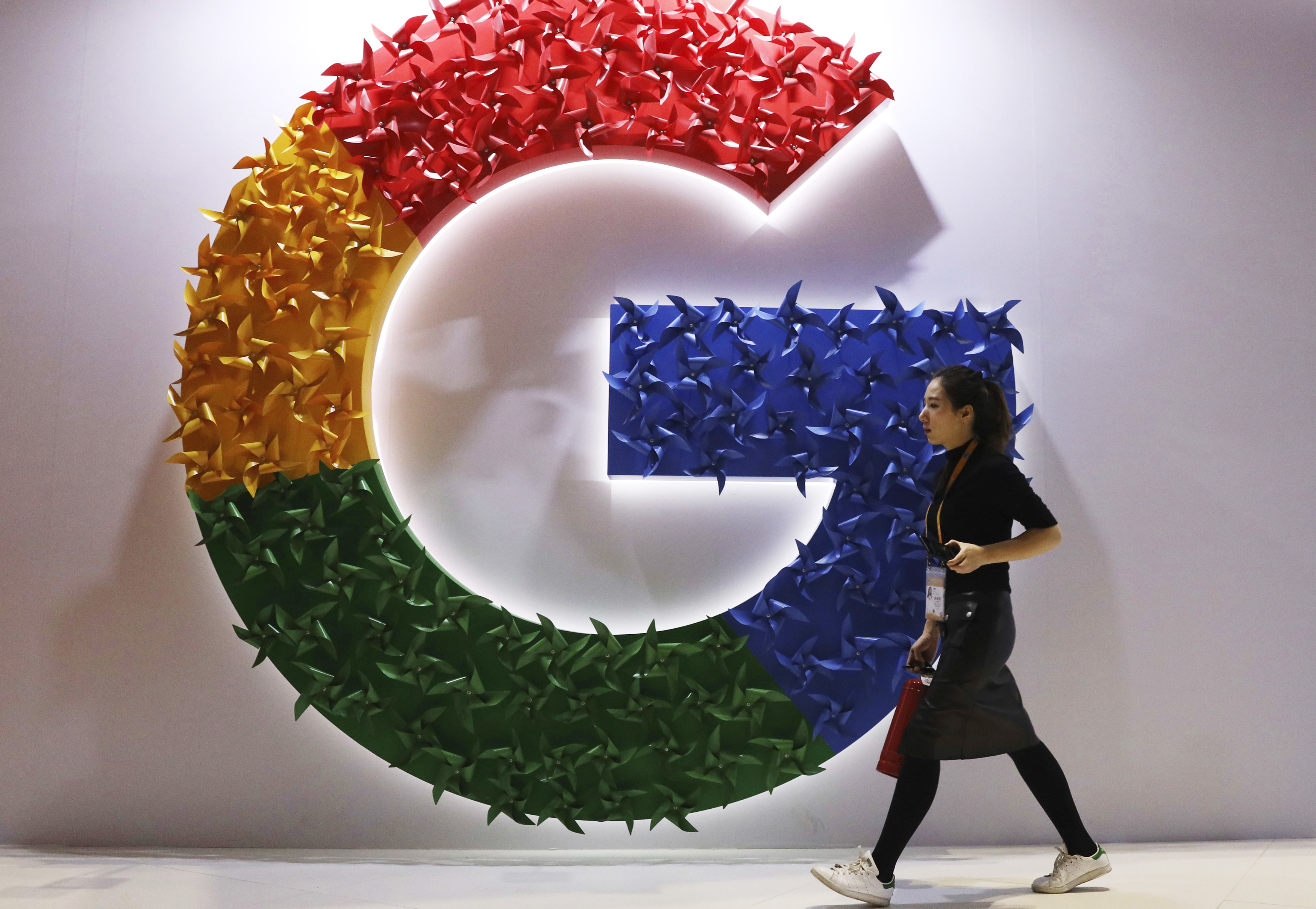 A woman walks past the logo for Google at the China International Import Expo in Shanghai.