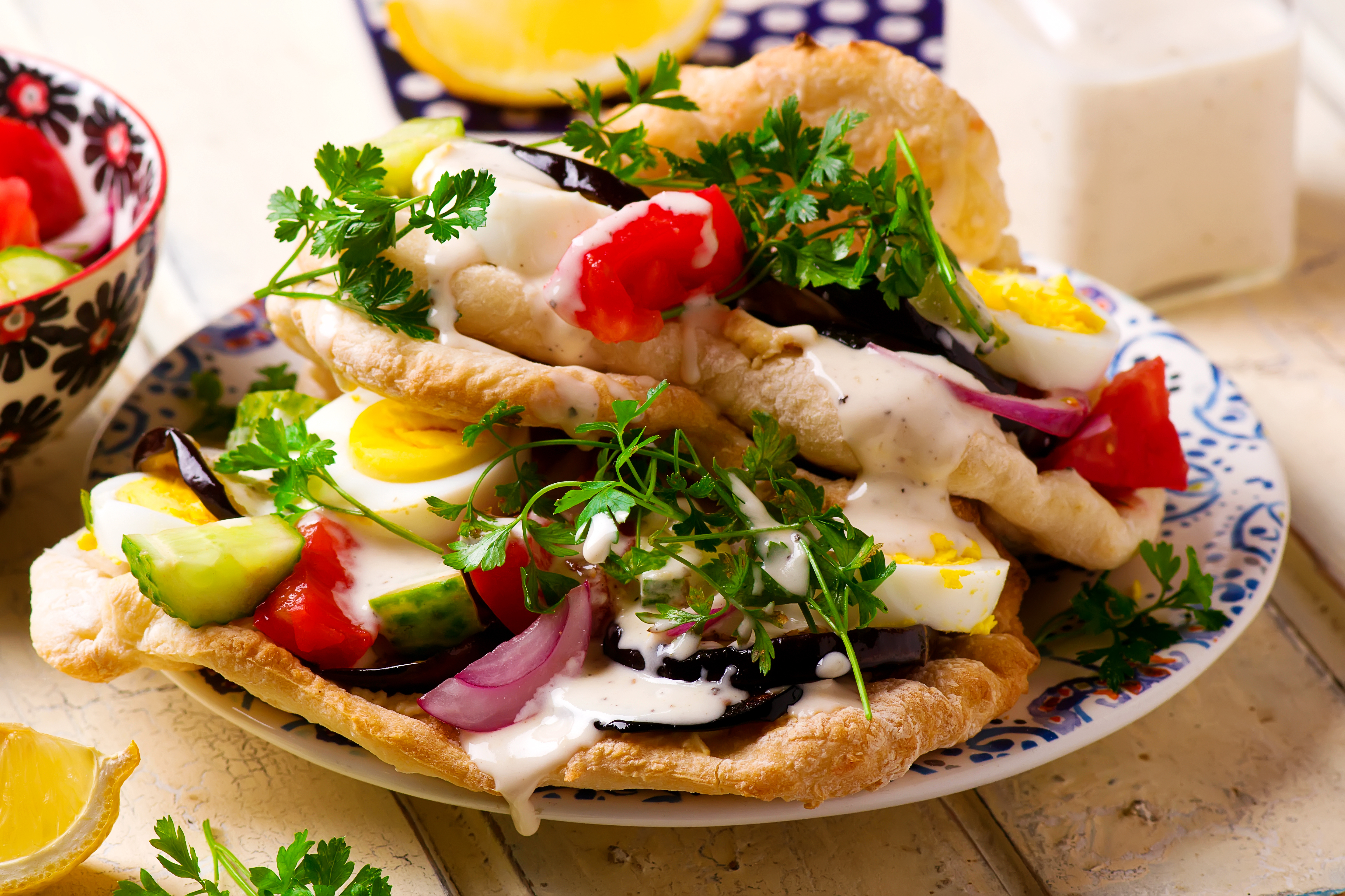 Pita bread filled with cucumber, tomato, onion, eggplant, sliced hard-boiled eggs, and yogurt sauce on a plate with parsley garnish.