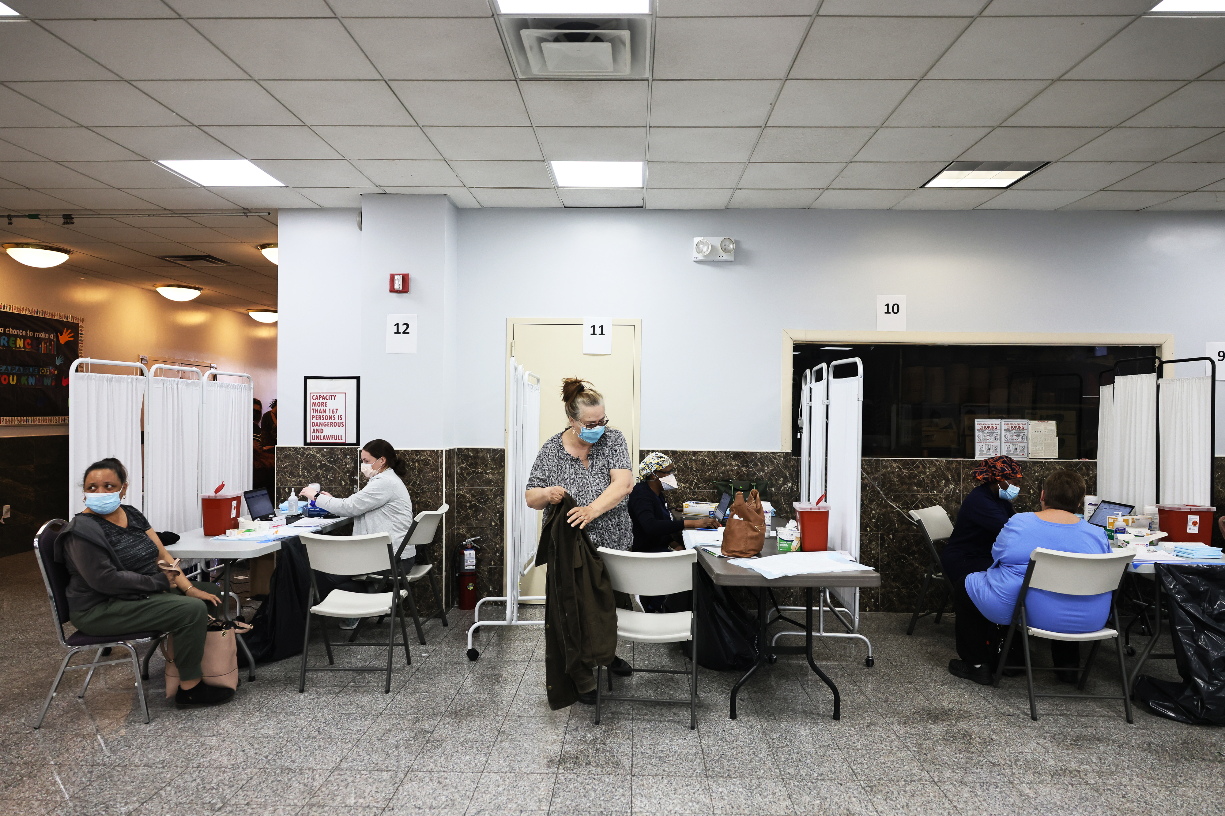 People receive COVID vaccines in an office space, with small white curtains separating recipients.