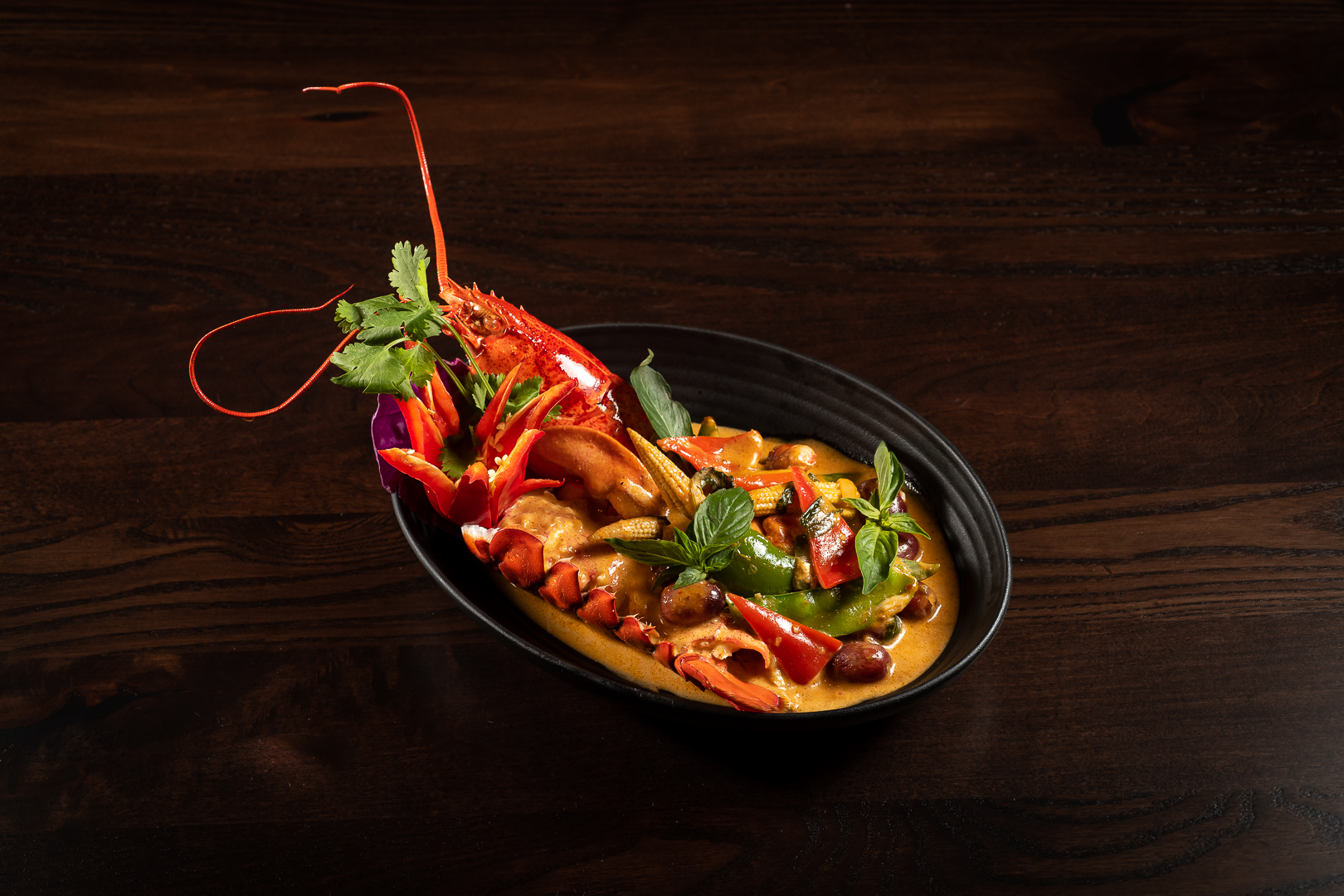 black bowl filled with lobster and bright curry sauce on a brown table