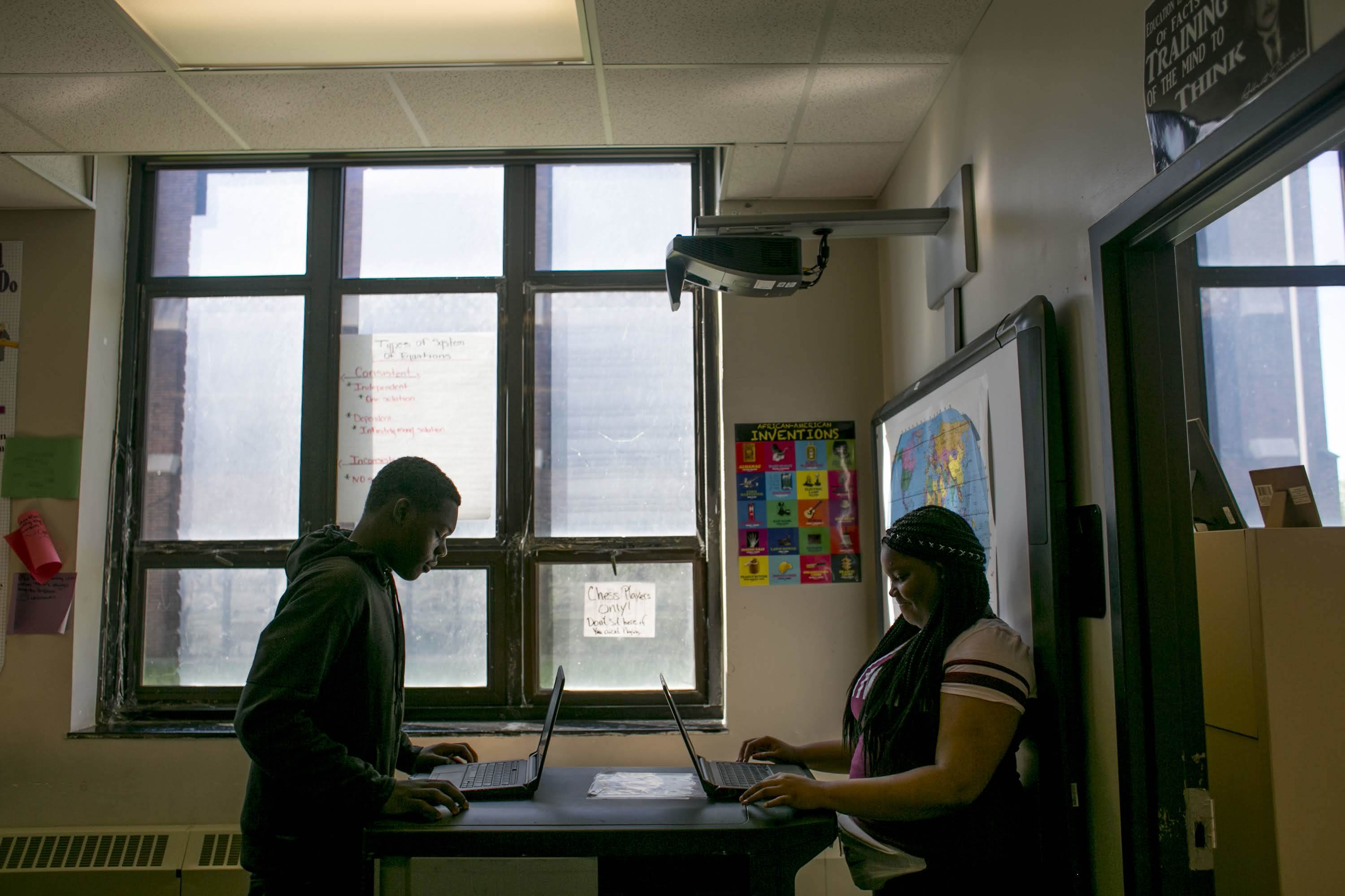 Two students work on their laptops in a classroom, partially silhouetted against a window.