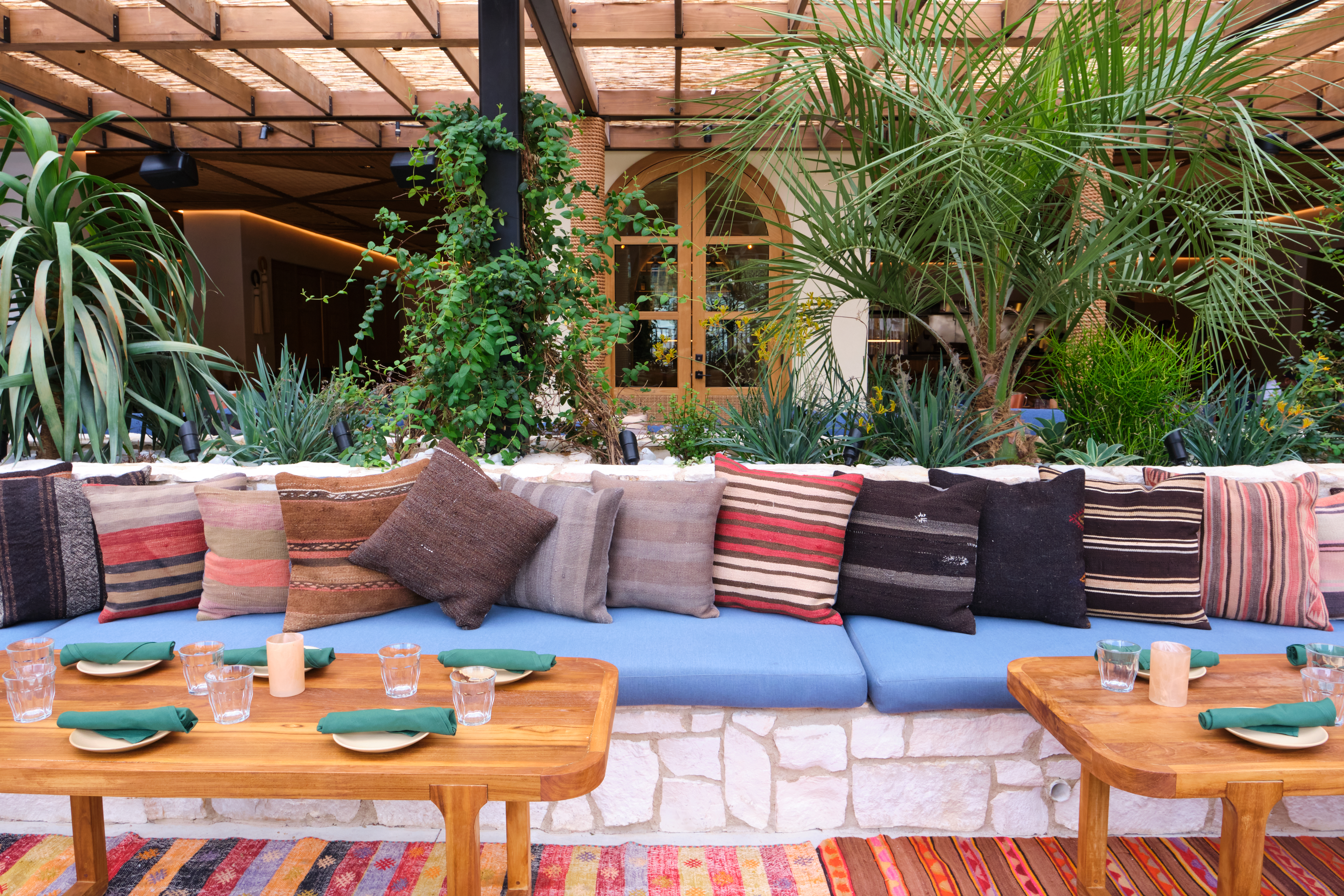 A patio with a blue banquette and pillows with wooden tables in front of it.