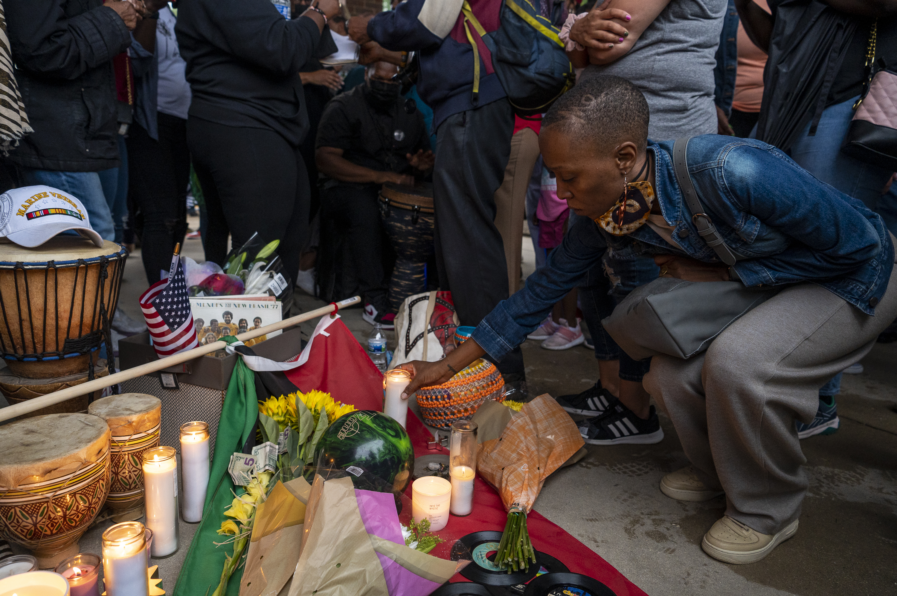 A women places a lit candle next to a memorial set up for Keith Cooper at Kimbark Plaza at 53rd Street and Kimbark Avenue on July 16. Cooper was punched in the head and killed during a attempted carjacking in the plaza.| Tyler LaRiviere/Sun-Times