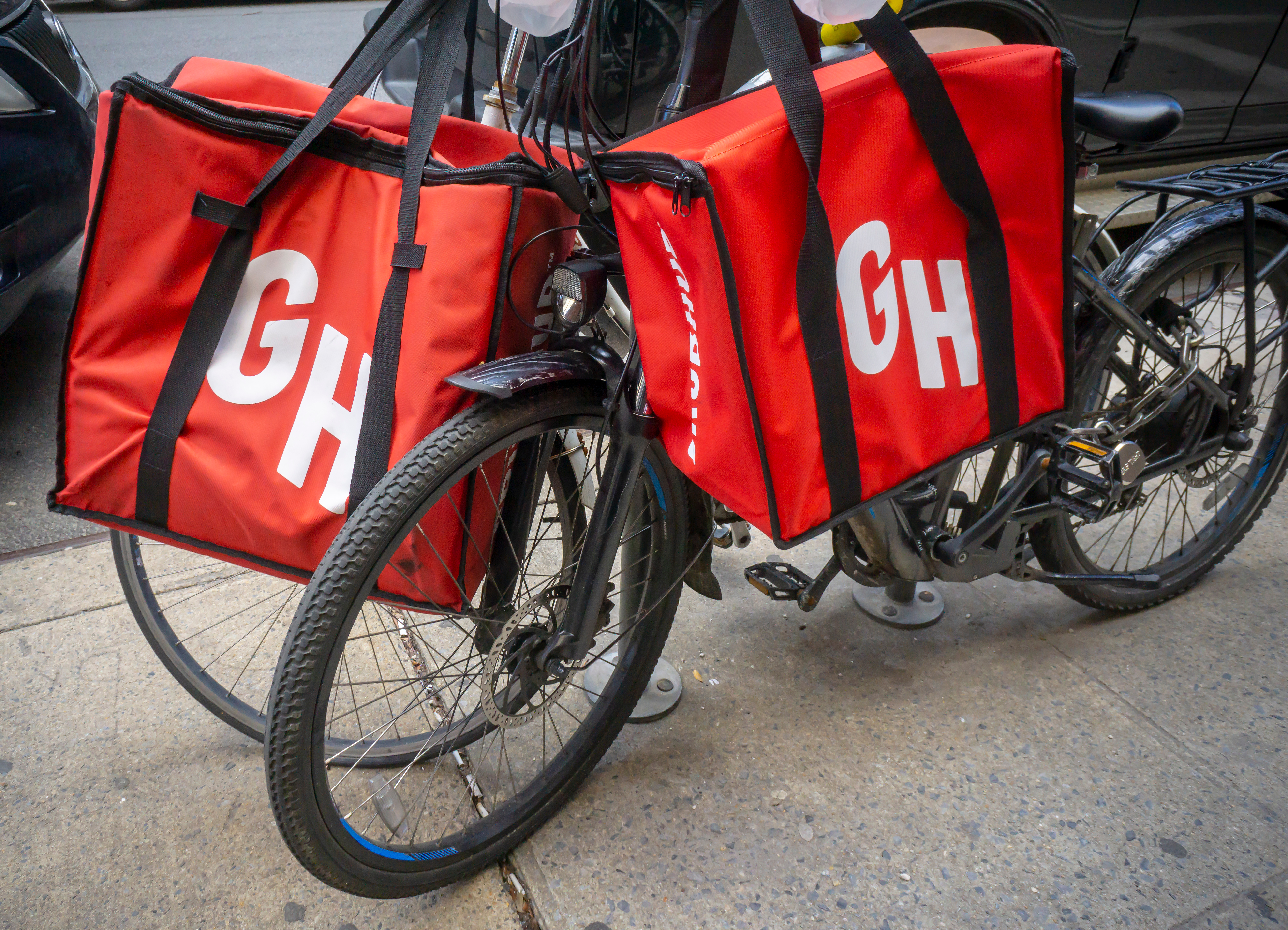 A stock photograph of a bicycle holding two red Grubhub food delivery insulated bags
