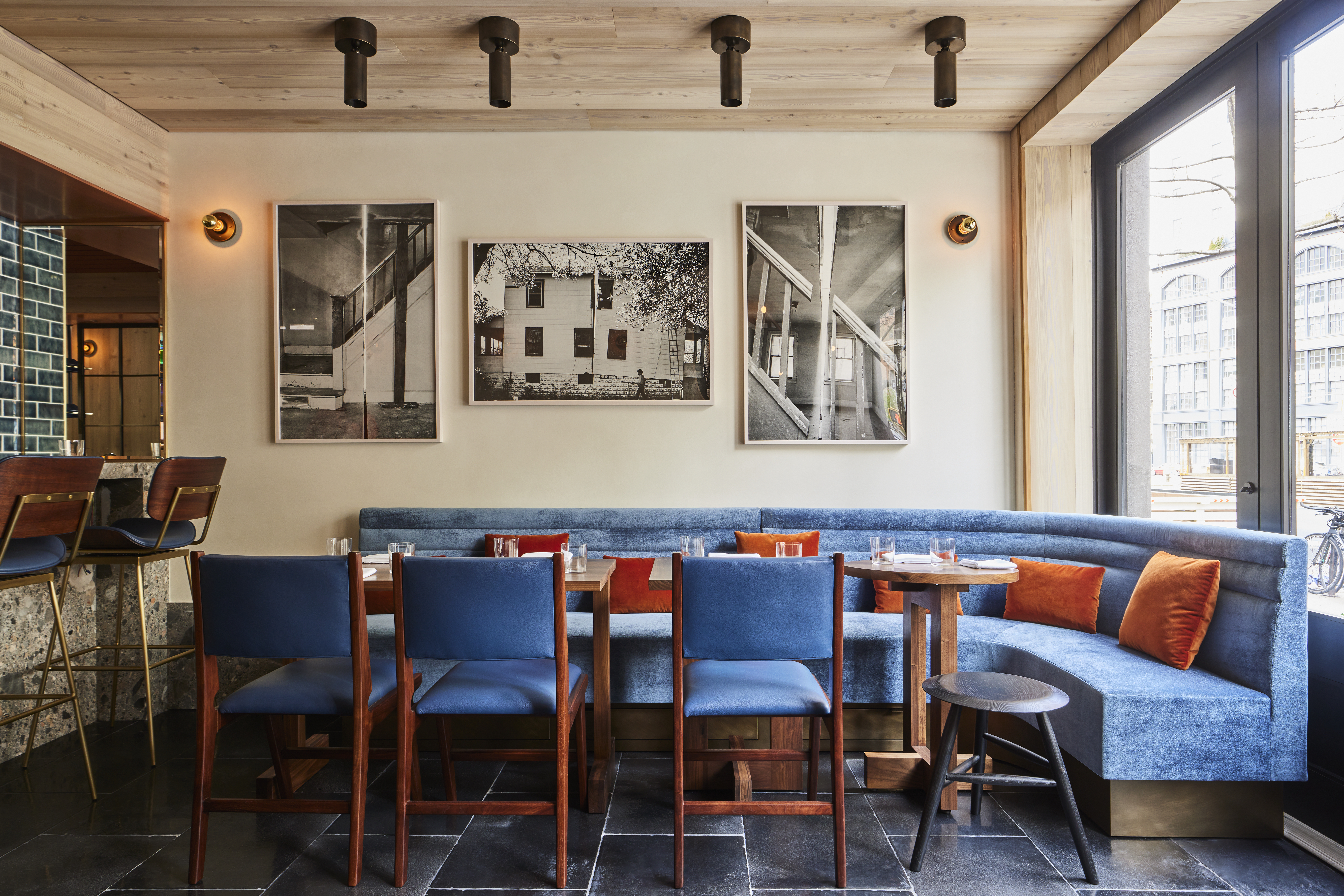 A well-lit dining room with a wrap-around, blue velvet banquette and a few wooden chairs