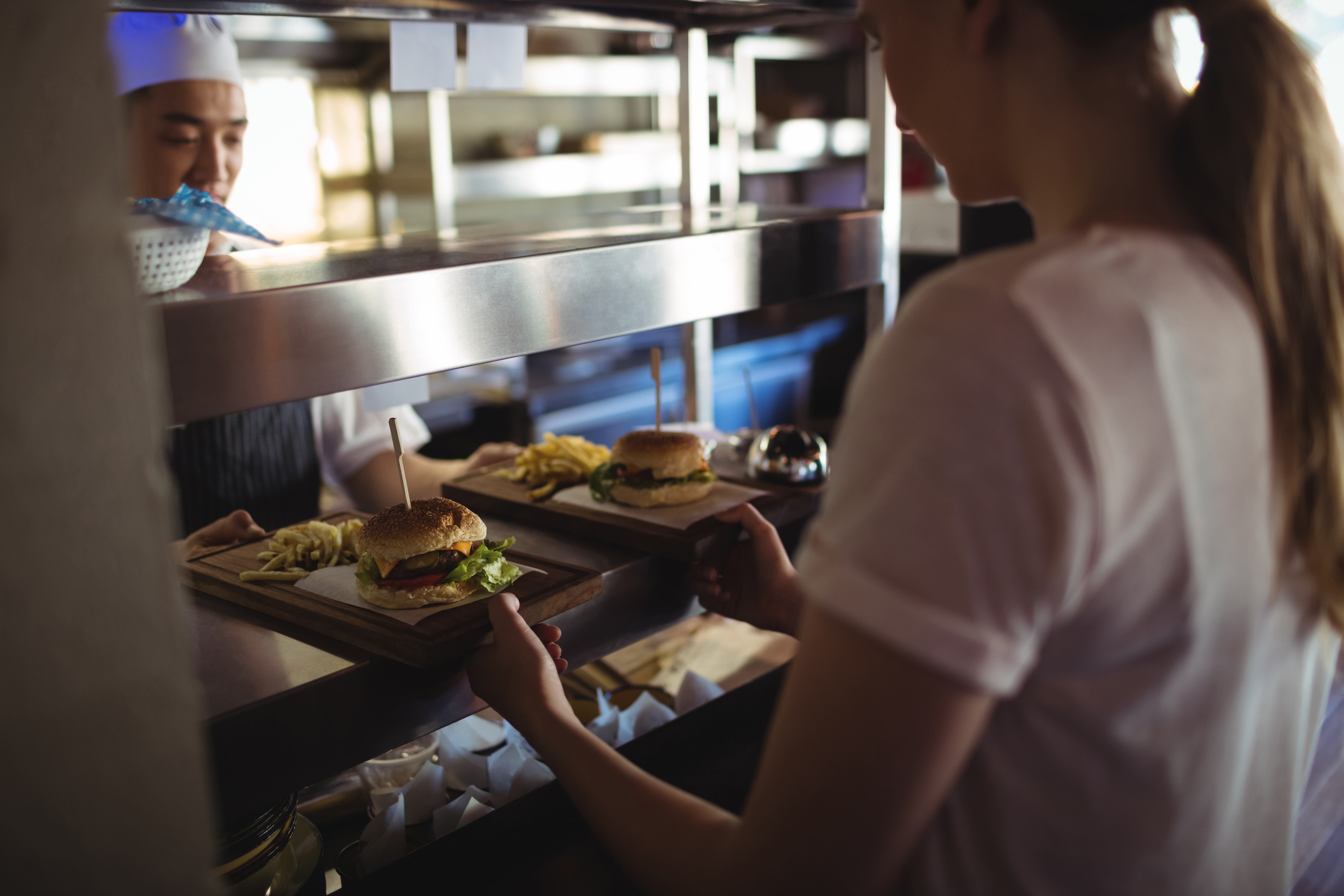 A server picks up two burgers from a pass in a restaurant.