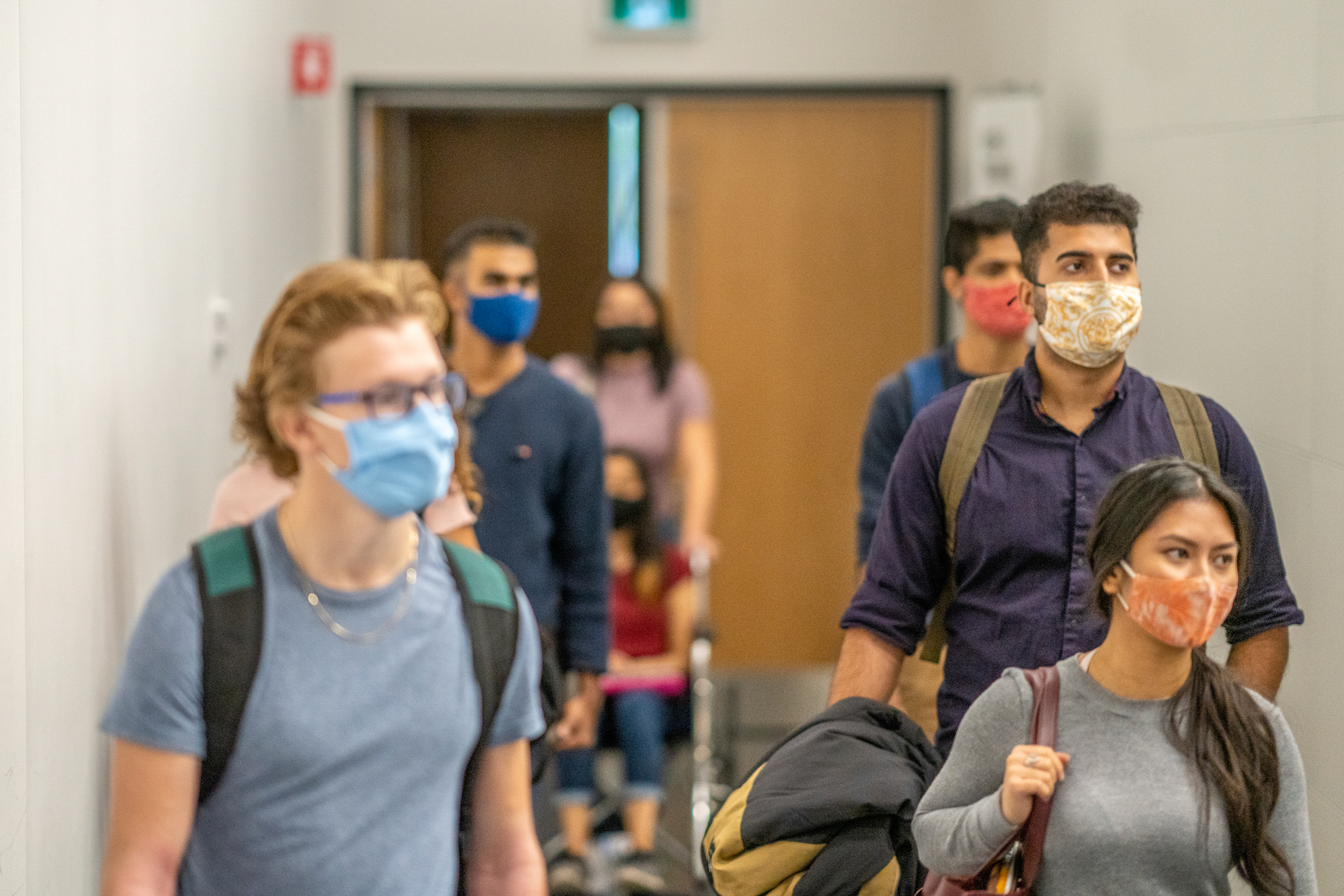 Students filing into class while wearing protective face masks.