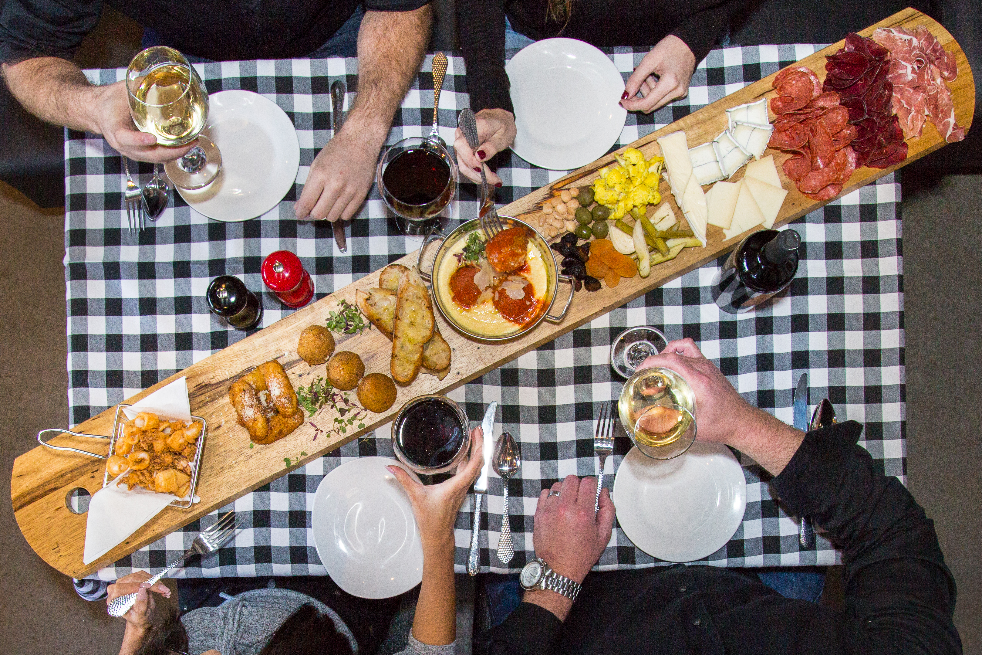 A table with a black and white checkered tablecloth is shown from above surrounded by hands holding wine glasses. A long wooden board with charcuterie stretches at an angle across the center of the table.