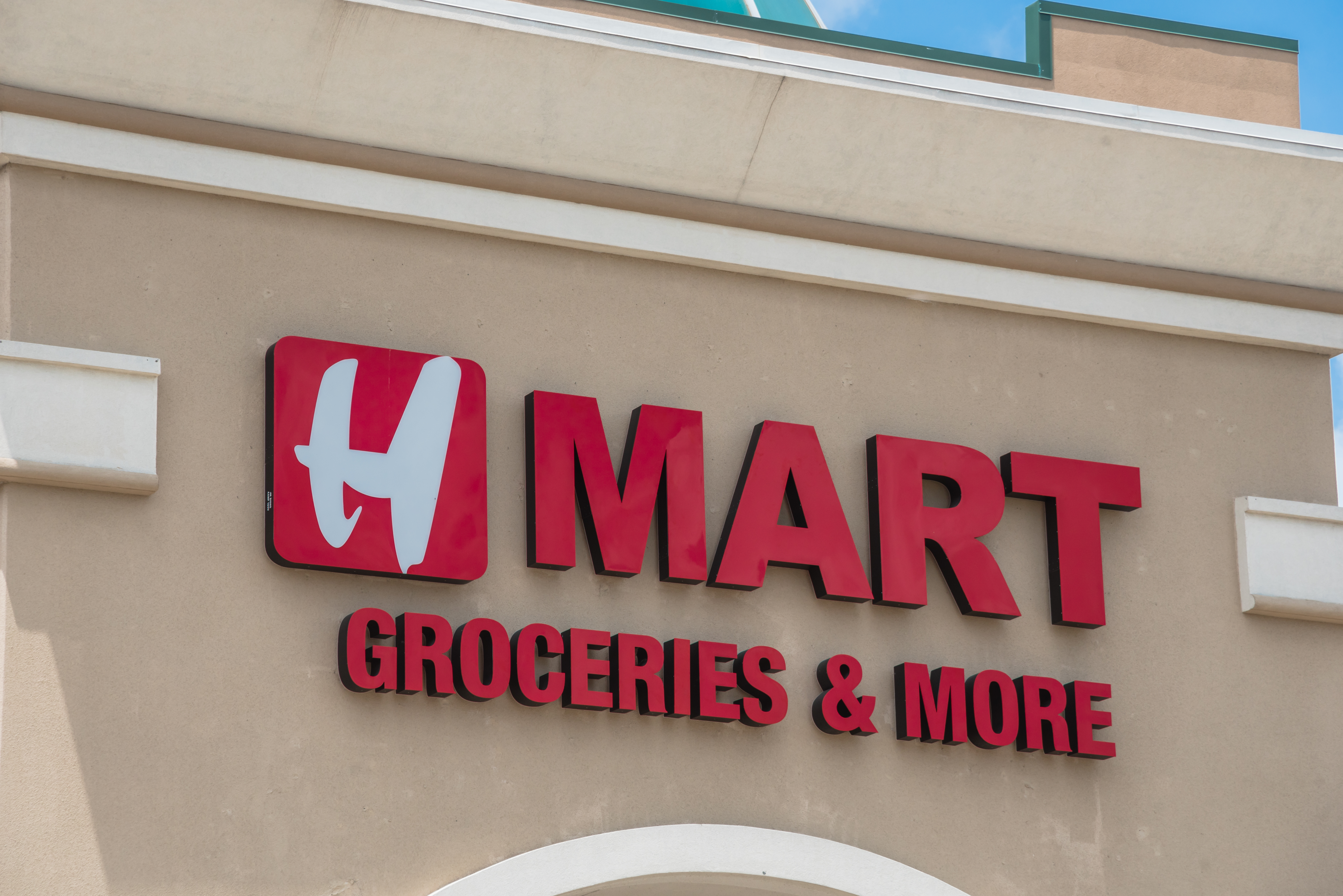 """A red sign says """"H Mart, groceries and more"""" on a beige facade, with the grocer's logo"""