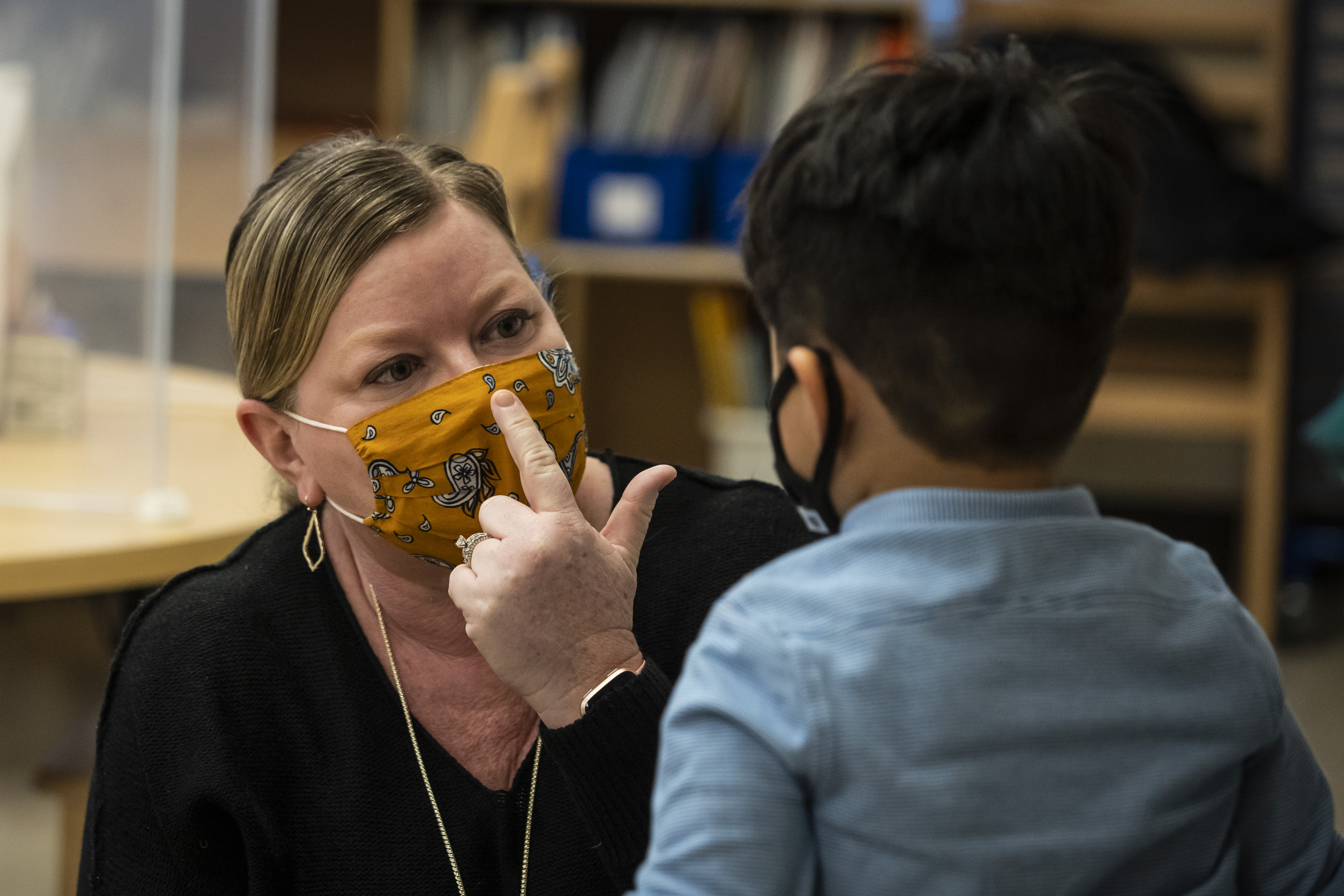 A Southwest Side preschool teacher shows a student how to properly wear a mask earlier this year. New CDC guidelines recommend masks for anyone inside a school regardless of vaccination status.
