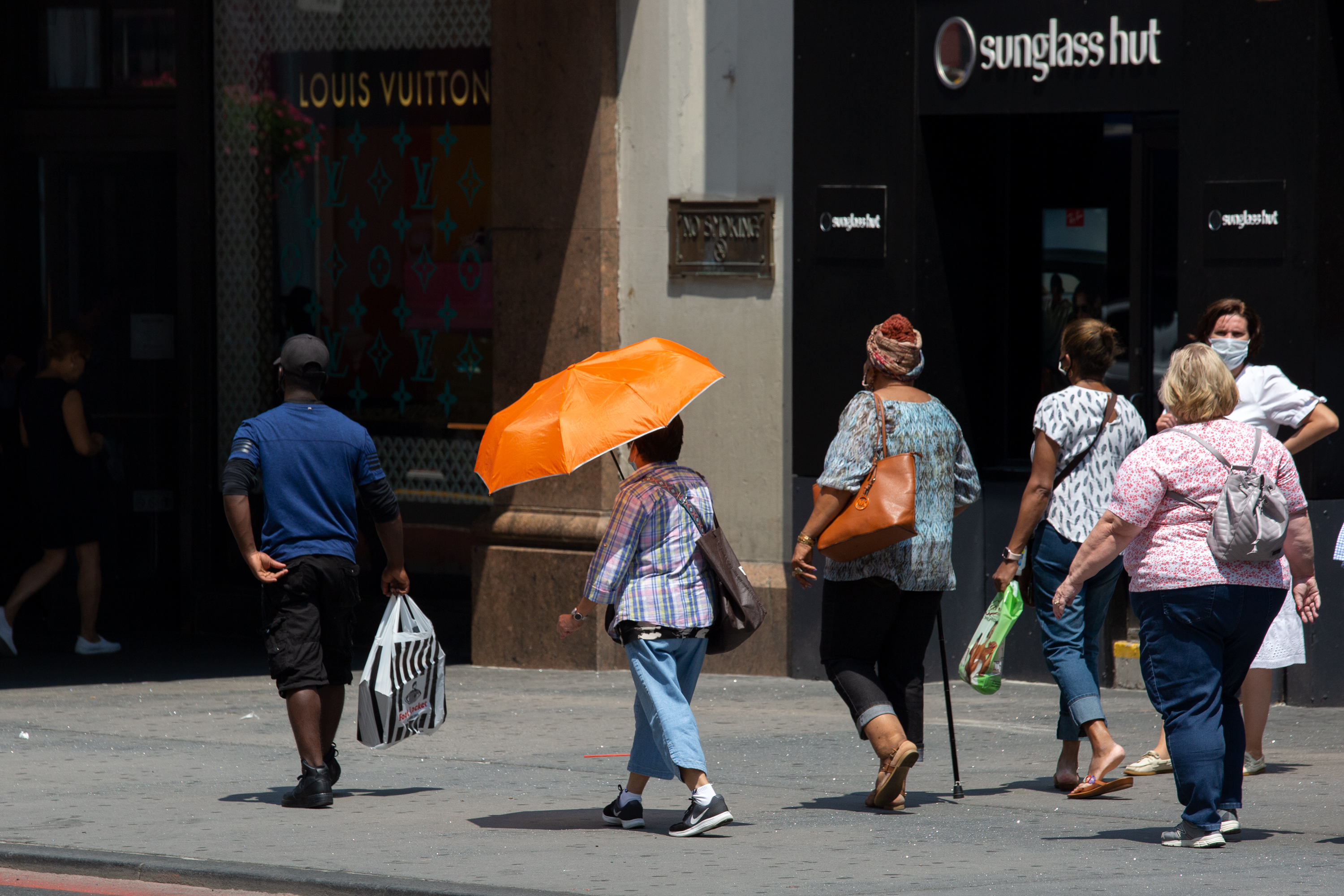 A woman shields herself from the blazing sun on West 34th Street, July 27, 2021.
