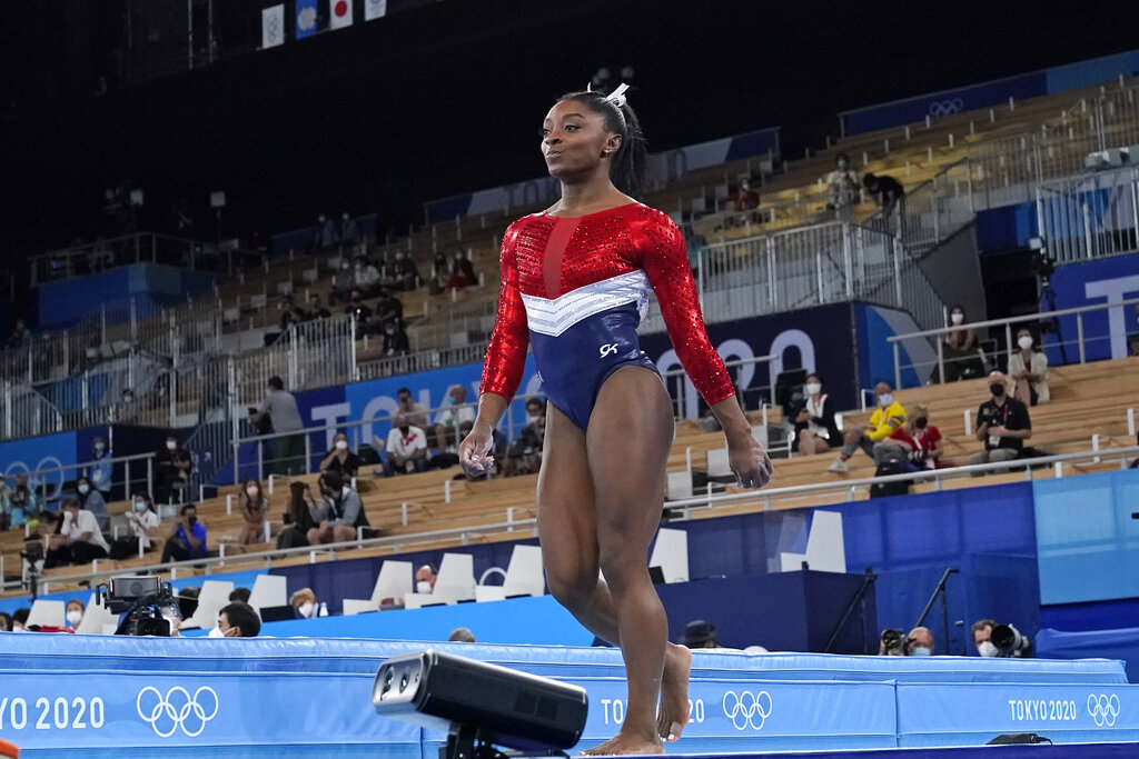 Simone Biles, of the United States, walks after performing on the vault.