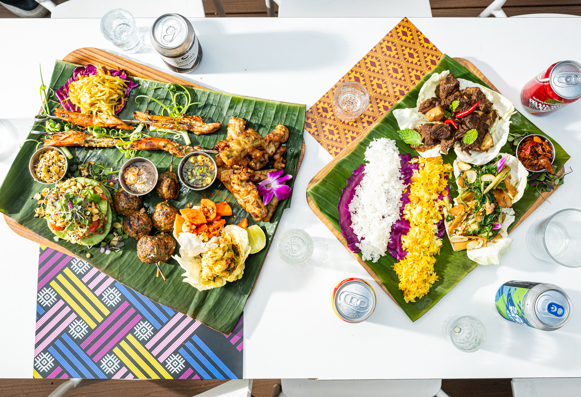 An overhead look at two trays full of Burmese dishes like gourd fritters, pork meatballs, grilled shrimp skewers, and tea leaf salad stacked in between green wontons