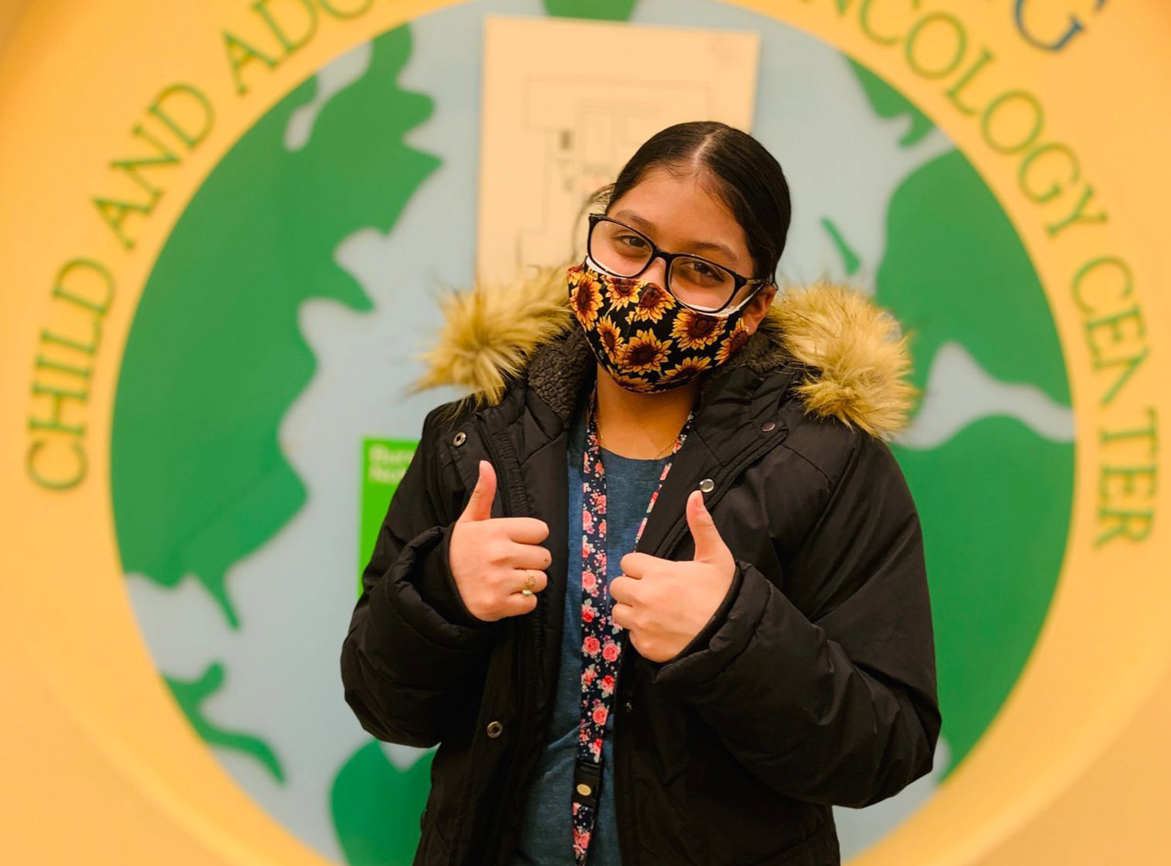 A young girl wearing a mask has two thumbs up in front of a sign.