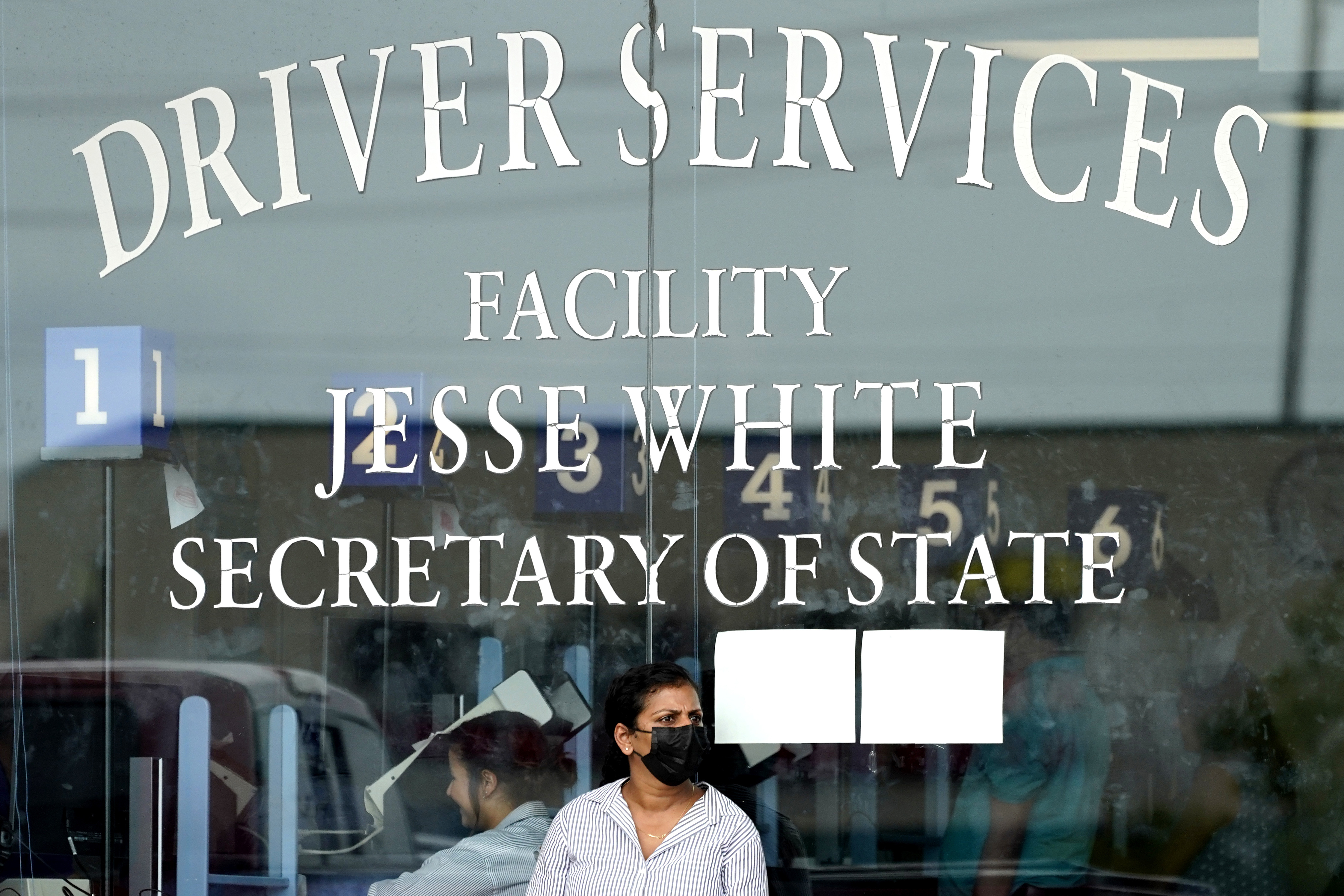 A woman wears mask as she waits to enter the Illinois Department of Motor Vehicles in Deerfield earlier this month. Masks will be required at all buildings managed by the Illinois Secretary of State starting Aug. 2.